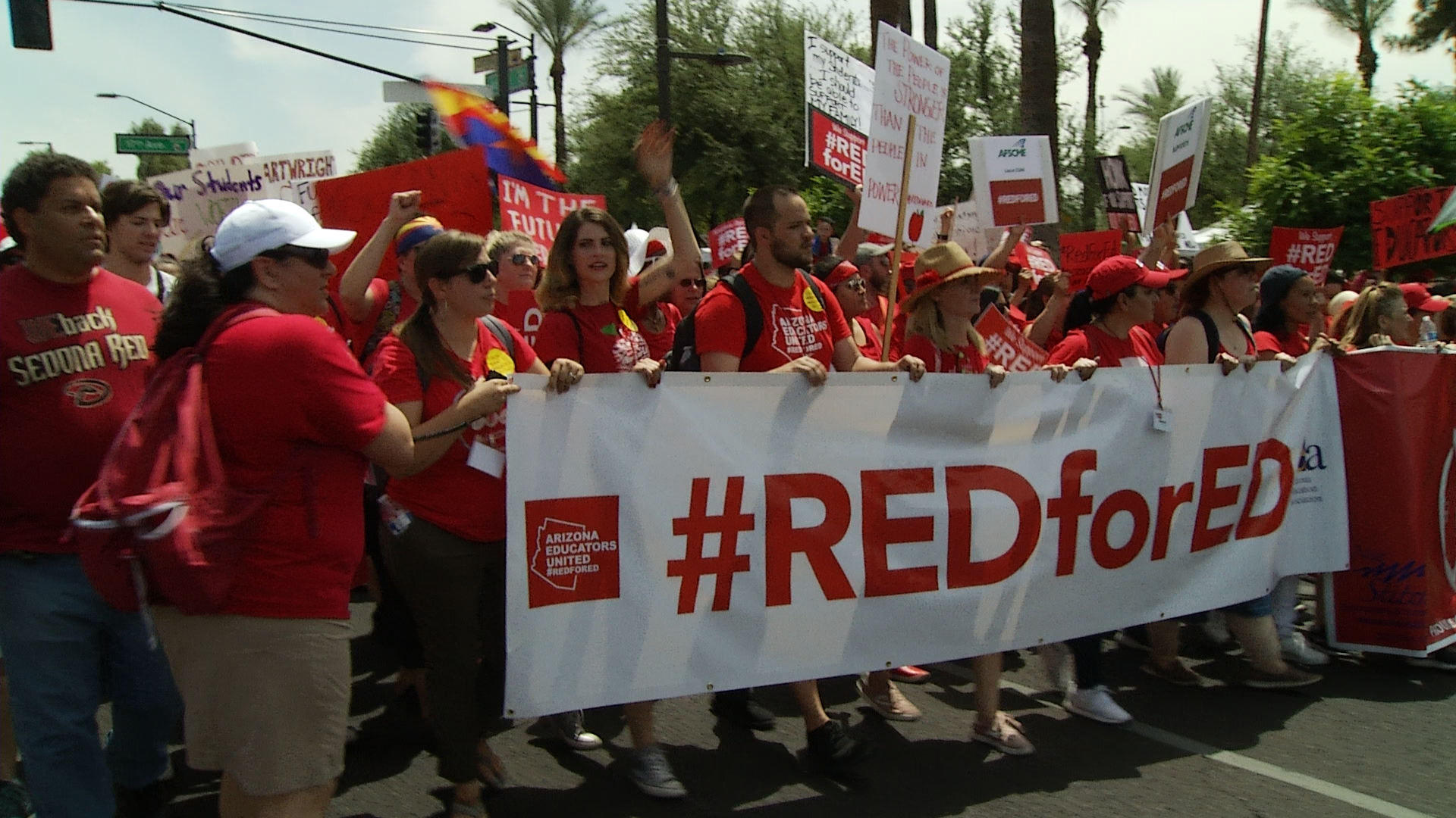 Demonstrators with the Red for Ed movement march to the Capitol in Phoenix.