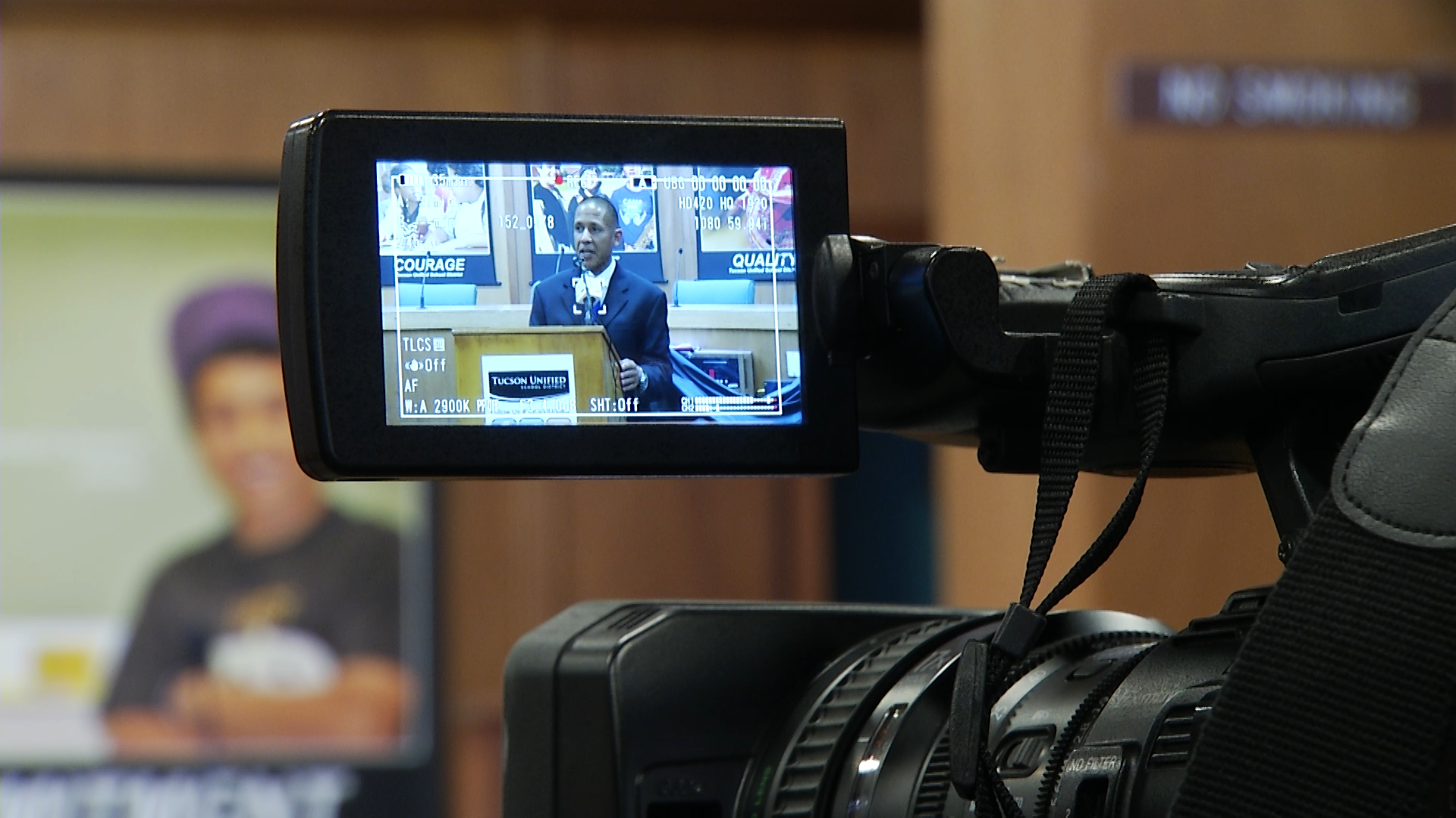 A camera's viewfinder captures Tucson Unified School District Superintendent Gabriel Trujillo speaking to reporters at a news conference at the district's headquarters.