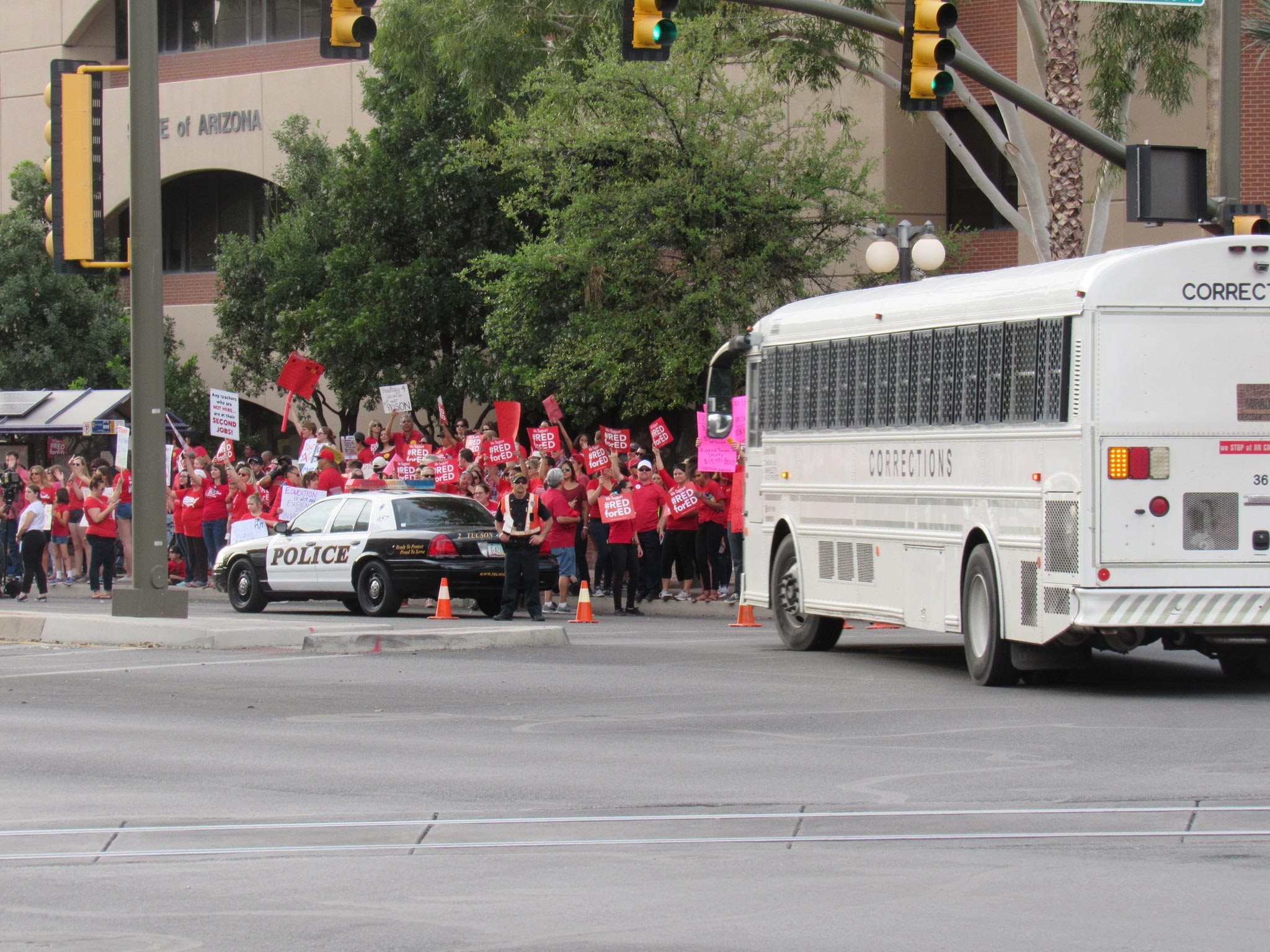 Corrections bus drives past rally