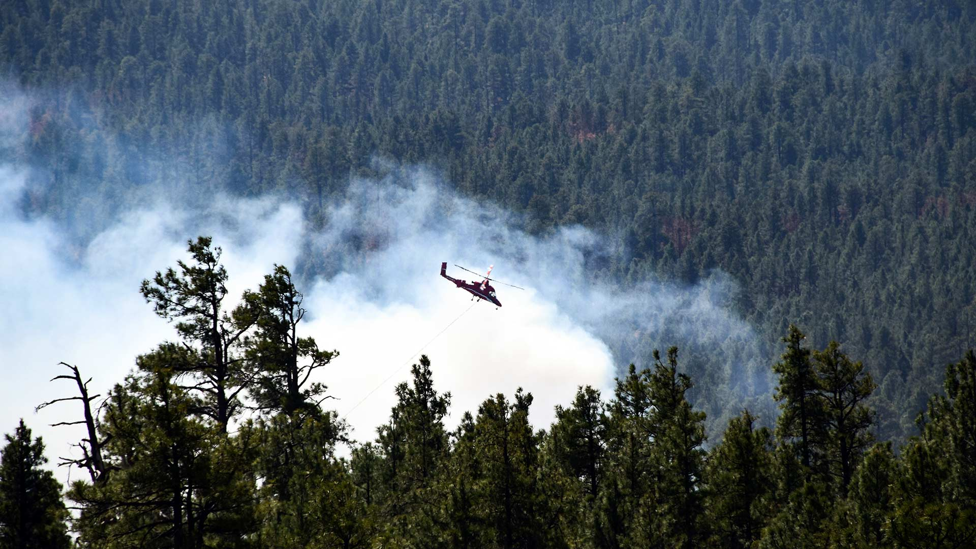 A helicopter helps battle the Tinder Fire, in north-central Arizona, April 30, 2018.