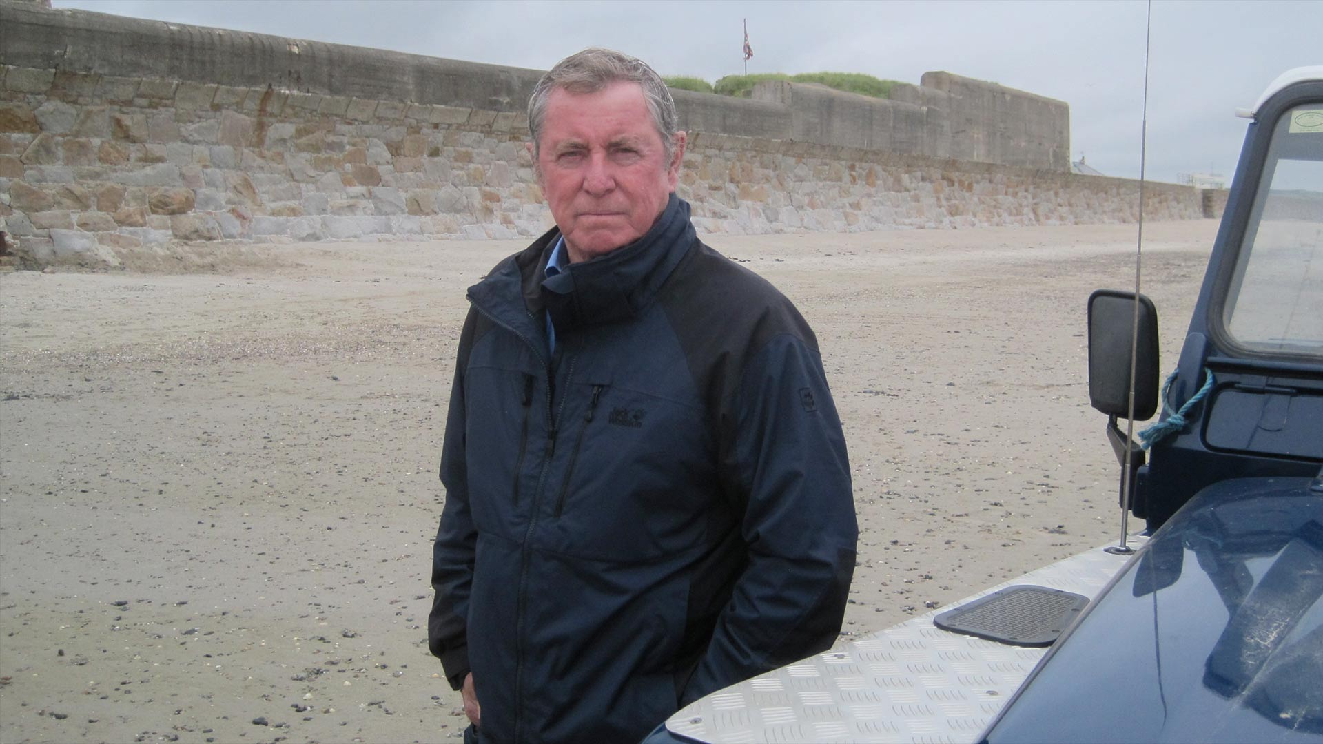 John Nettles standing next to his Land Rover.