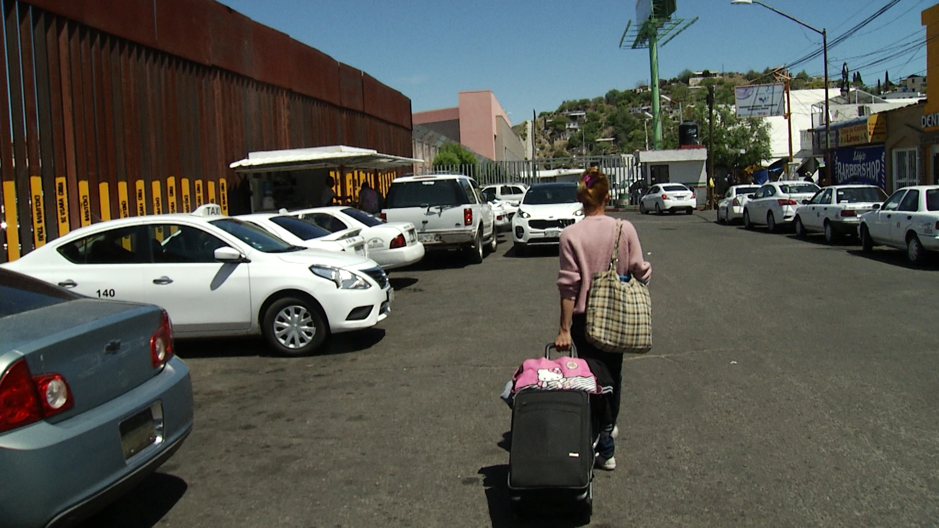 Nicol carries her luggage to the port of entry in Nogales to seek asylum.