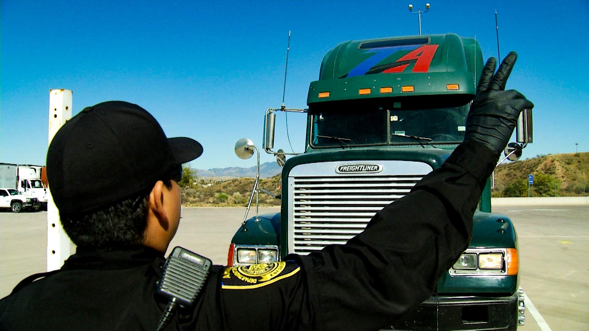 A semi truck undergoes a safety inspection at the Arizona-Mexico border.
