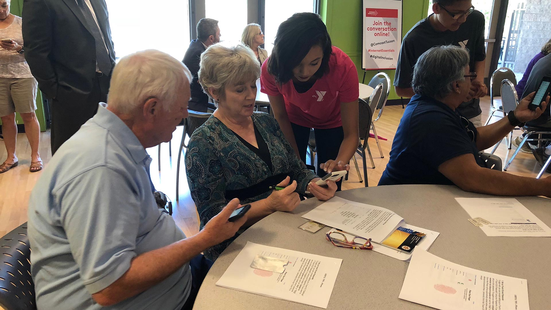 Joy Mona, 19, teaches two seniors how to navigate their iPhones at a pilot Teeniors workshop at the Northwest YMCA in Tucson.