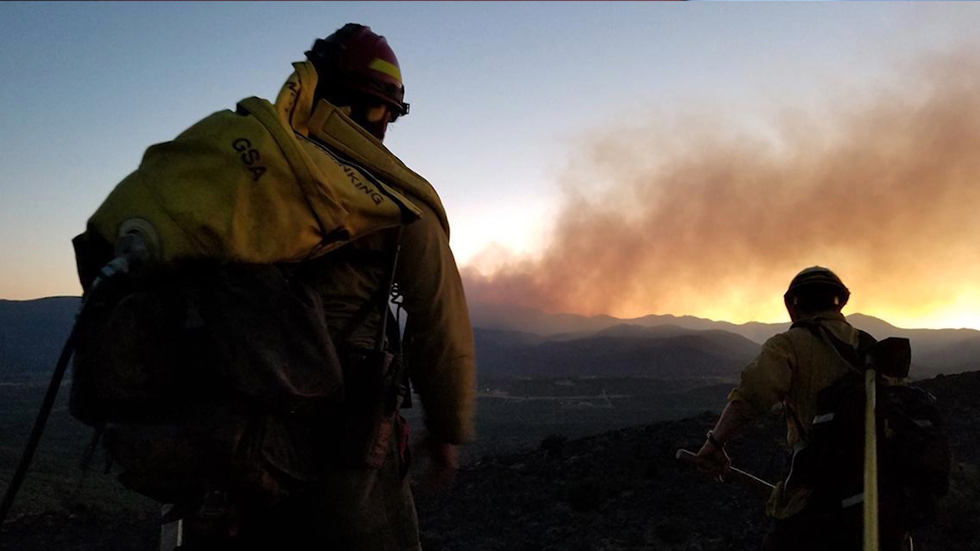 Wildland firefighters watch smoke from a wildfire.