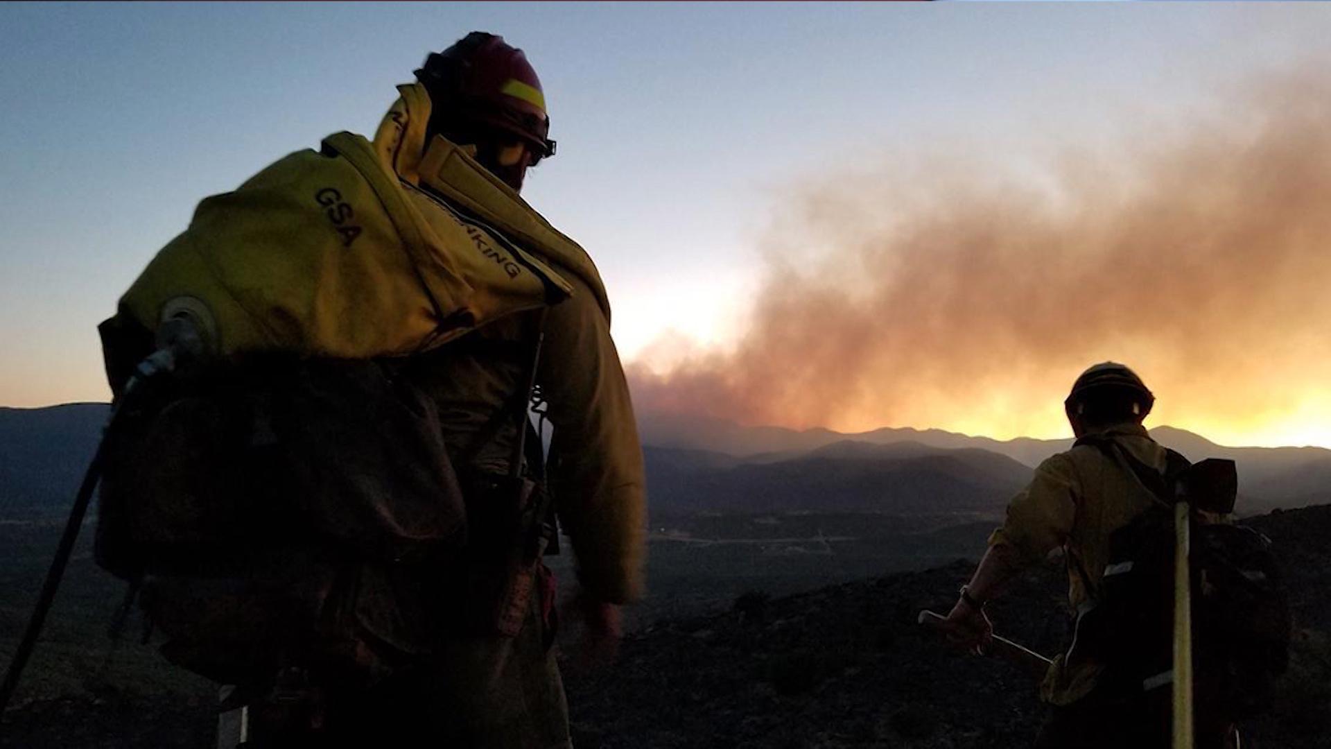 Wildland firefighters watch smoke from a wildfire.