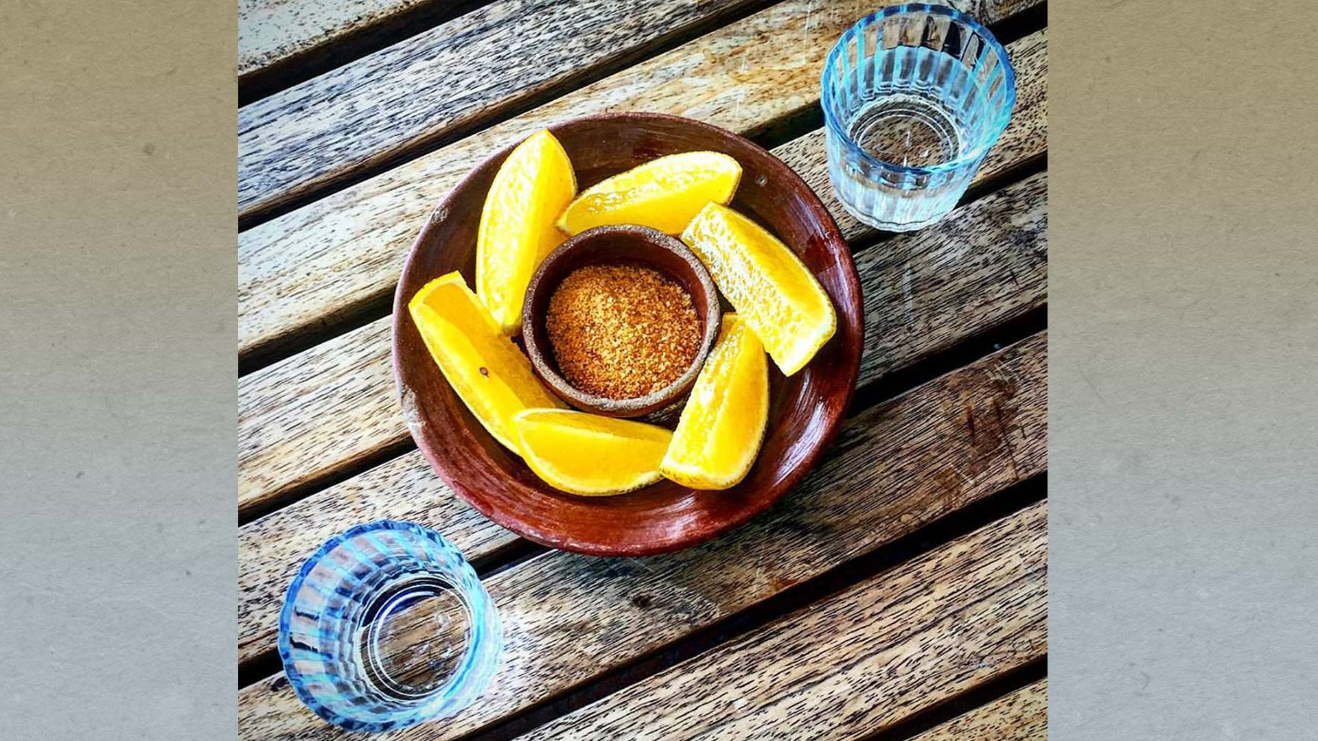 "Mezcal is traditionally served in shot glasses with orange slices covered in chilli powder or ""sal de gusano."""