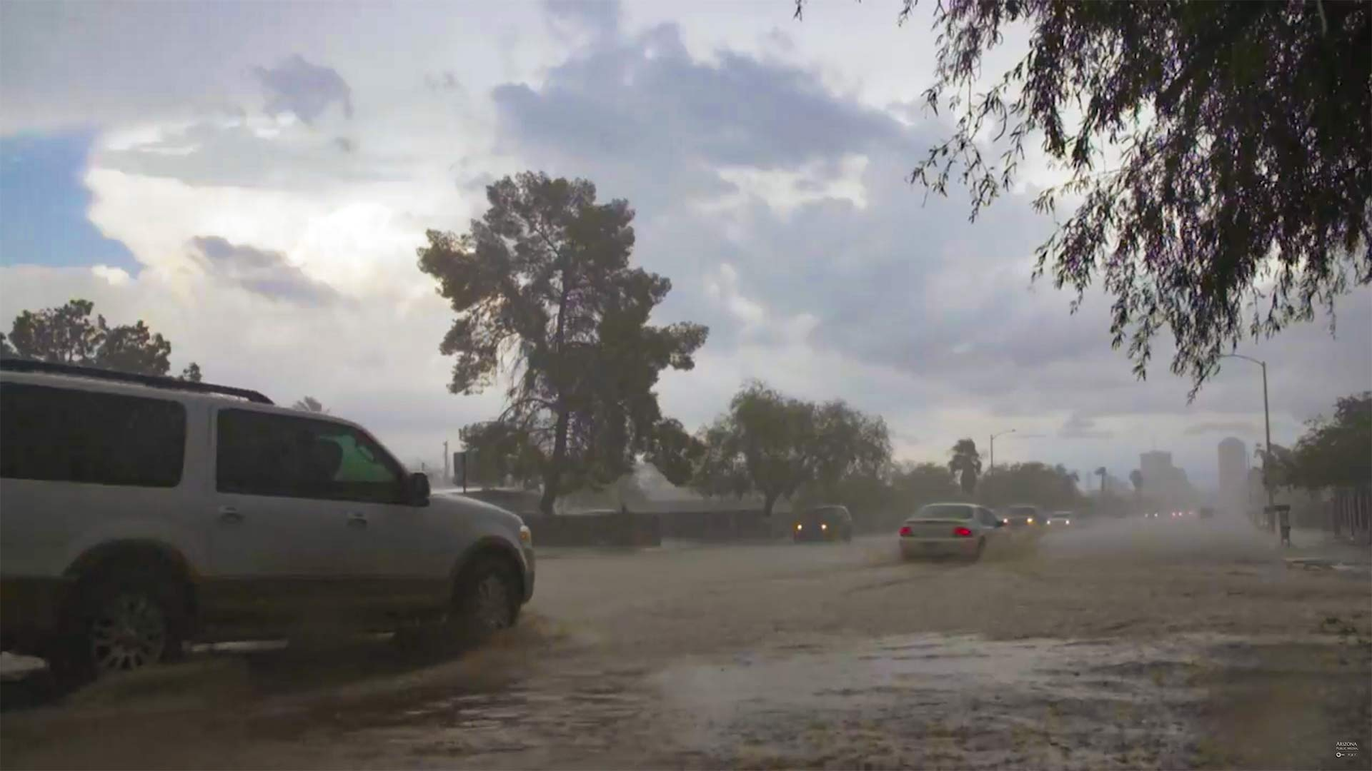 Cars drive through Tucson streets flooding with monsoon rains.