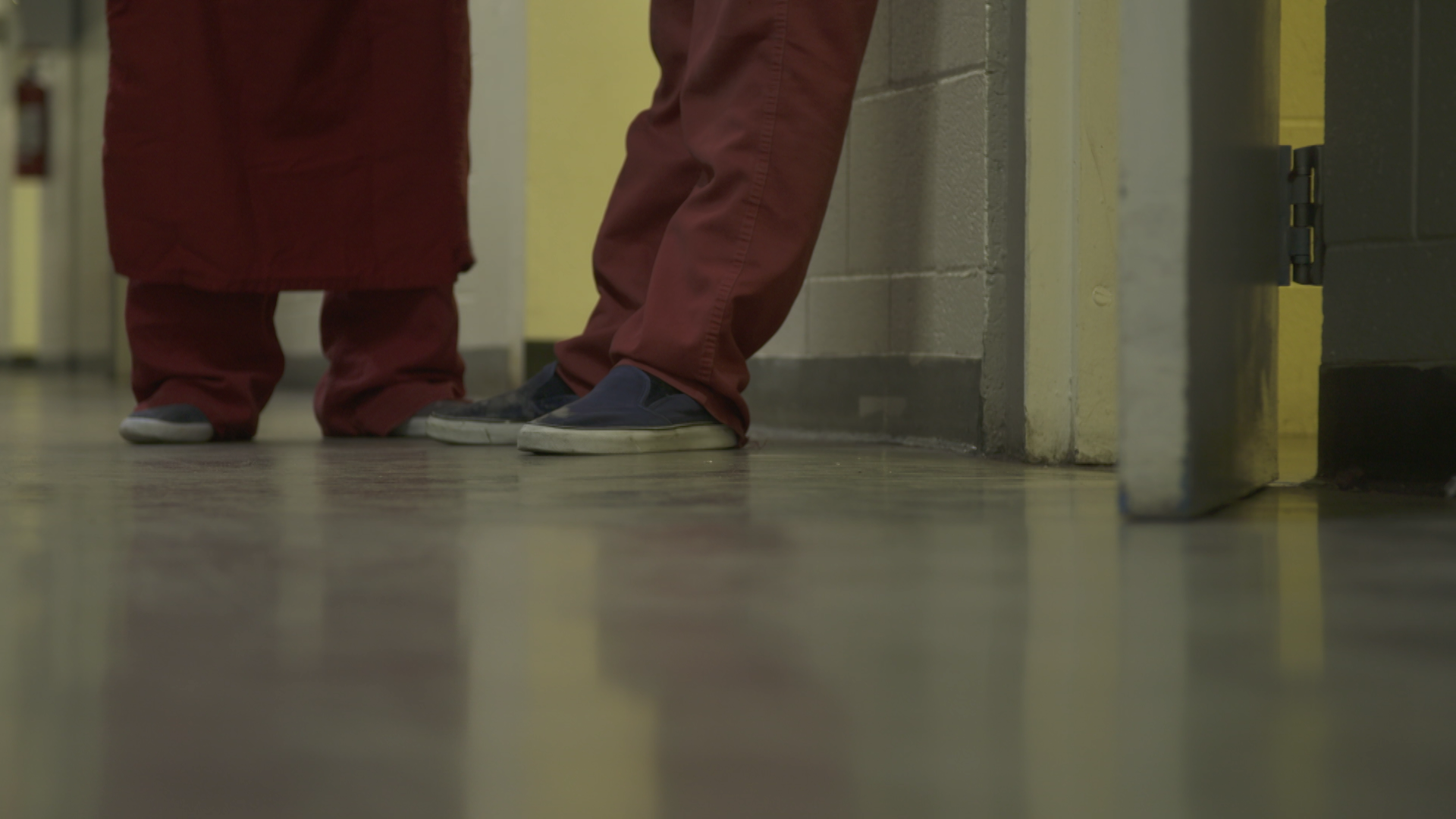 Two inmates stand in a hallway at the Pima County Jail.