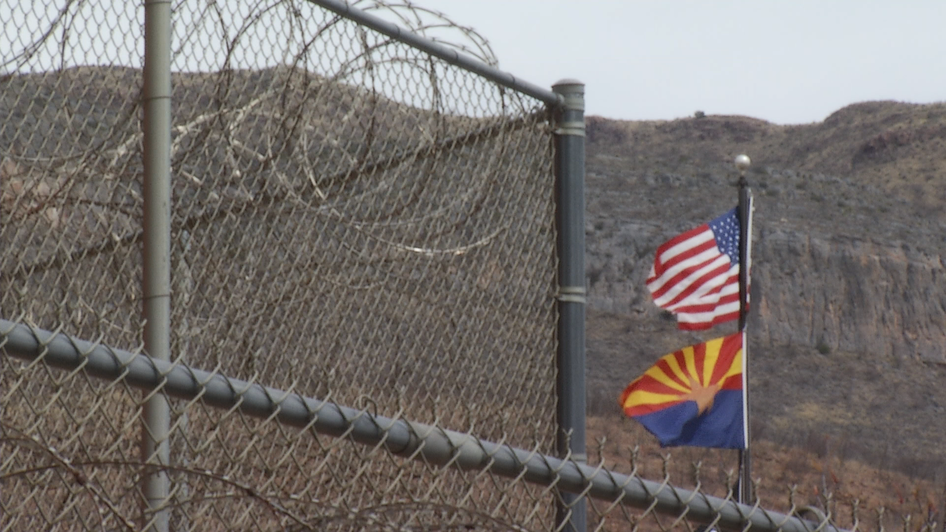 Flags for Arizona and the United States wave in the wind outside the Cochise County Jail.