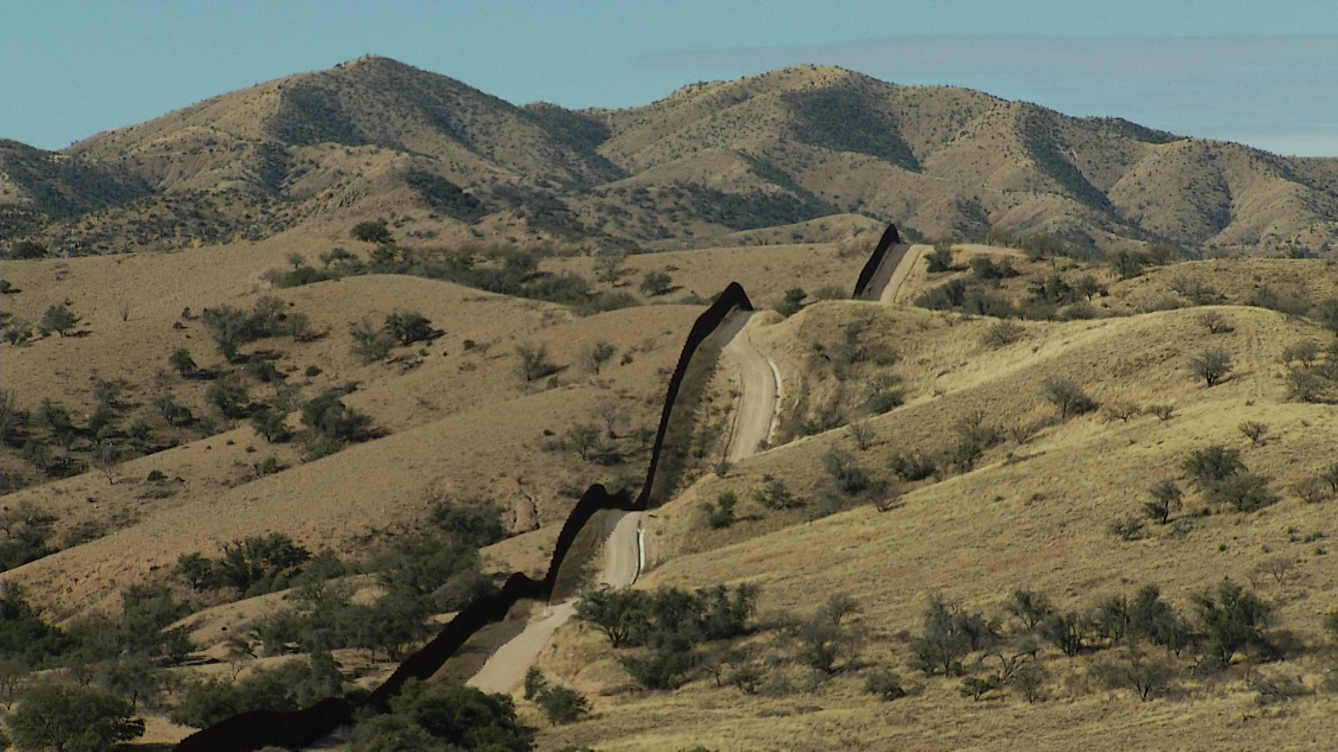 The border fence passes over hills on the line between Arizona and Mexico.