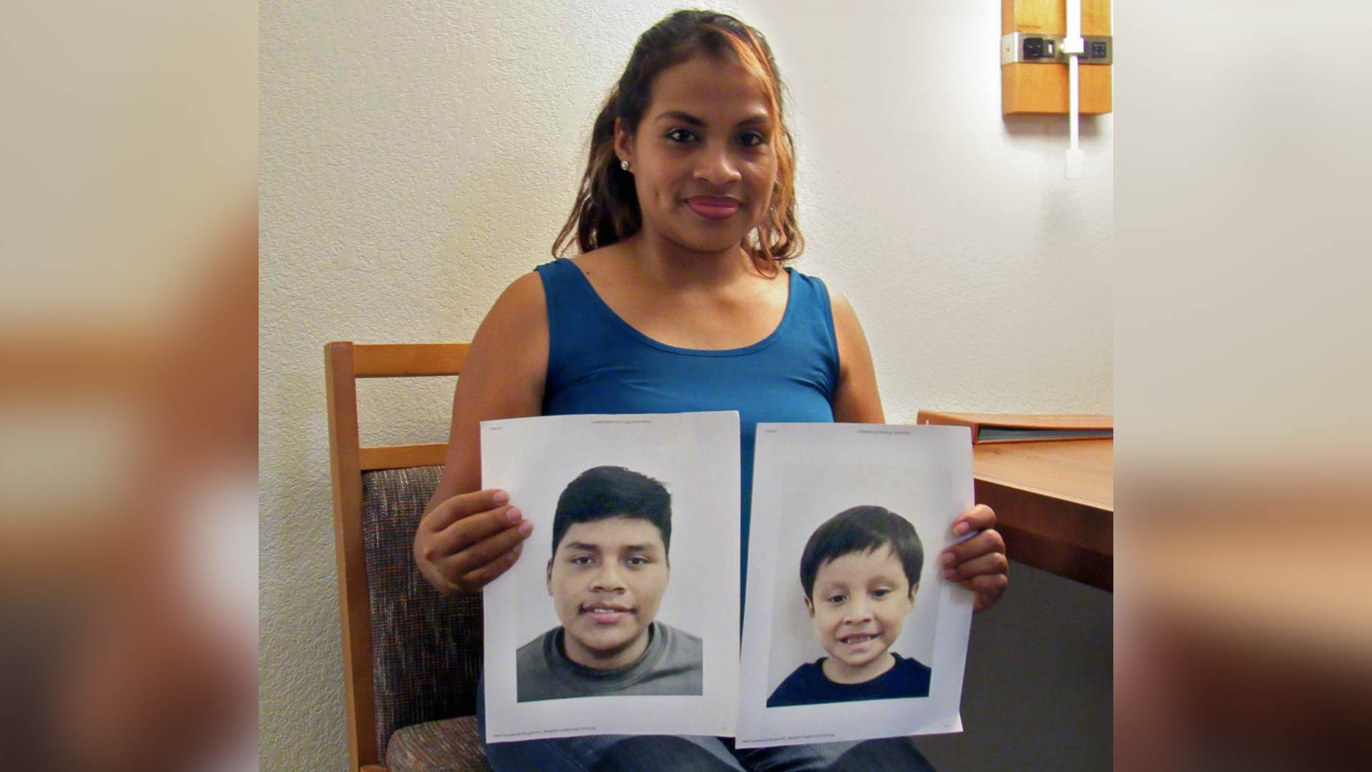 Rosaira Pablo Cruz holds photos of her two sons. Pablo Cruz was planning to catch a red-eye flight to New York Thursday night, with the hope of seeing the boys for the first time in about three months.