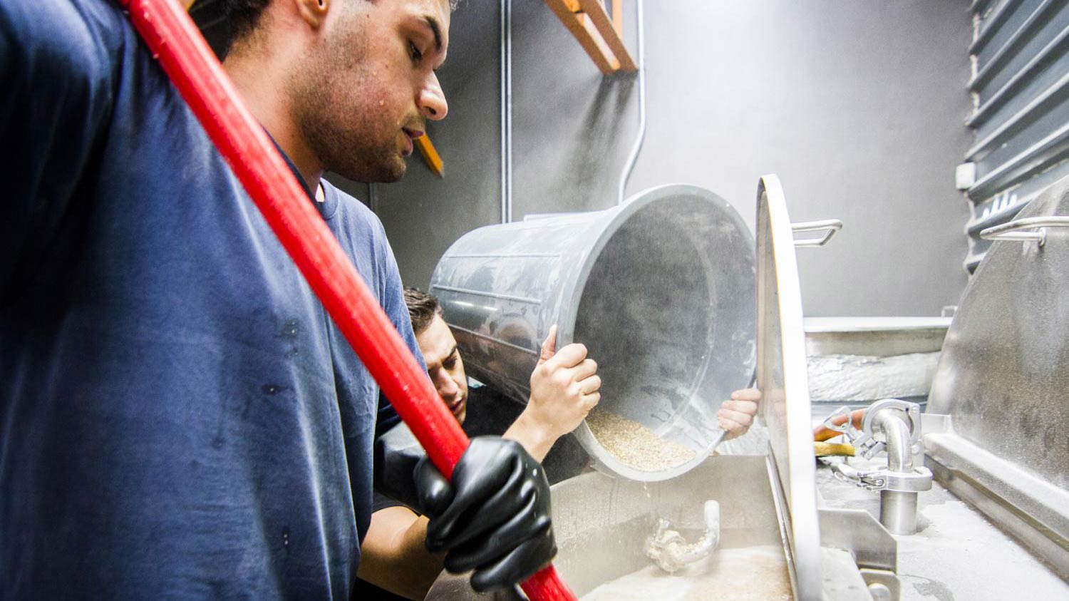Buqui Bichi Brewing assistant brewer Sergio Francisco Hernández stirs a batch of Sahuaripa IPA while head brewer Damian Erro adds grains.