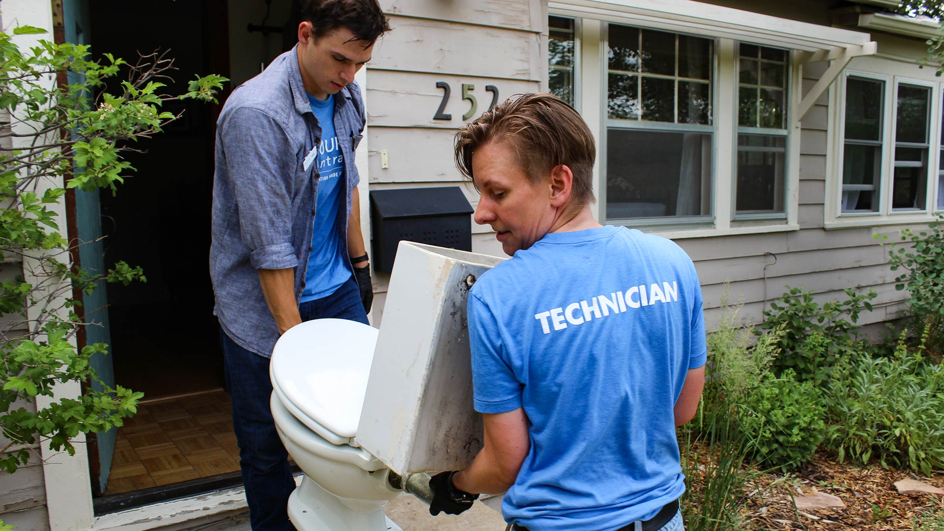 Resource Central employees Max Hartmann, left, and Neka Sunlin haul the MacFarland family's vintage toilet out of their Longmont, Colorado home.