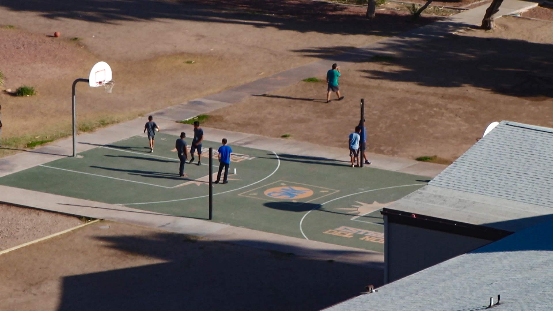 Kids play on a basketball court at the Southwest Key facility in Tucson, July 7, 2018