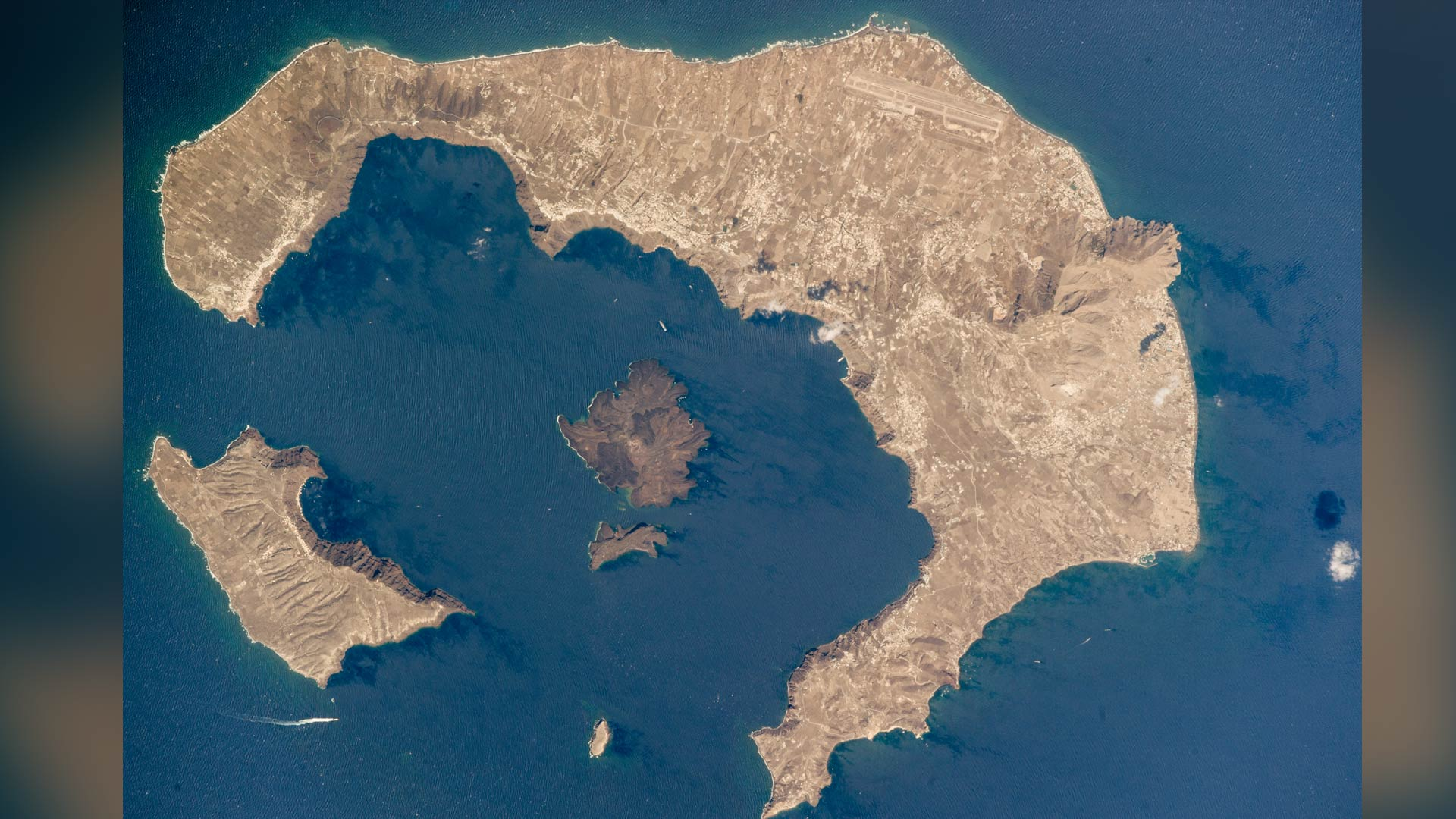 The largest island in the ring is the tourist mecca of Santorini (also known as Thira), while the other islands are Thirasia and Aspronisi. The three pieces are what remains after an enormous eruption destroyed most of a volcanic island. Courtesy of NASA Earth Observatory.