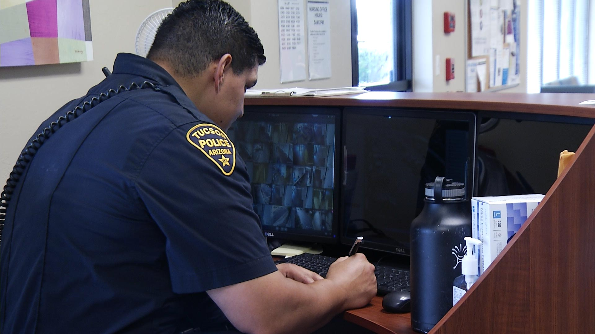 A Tucson Police officer reviews security footage at CODAC's treatment facility on August 22, 2018. The center offers medicated assisted treatment to help patients detox from opioids.