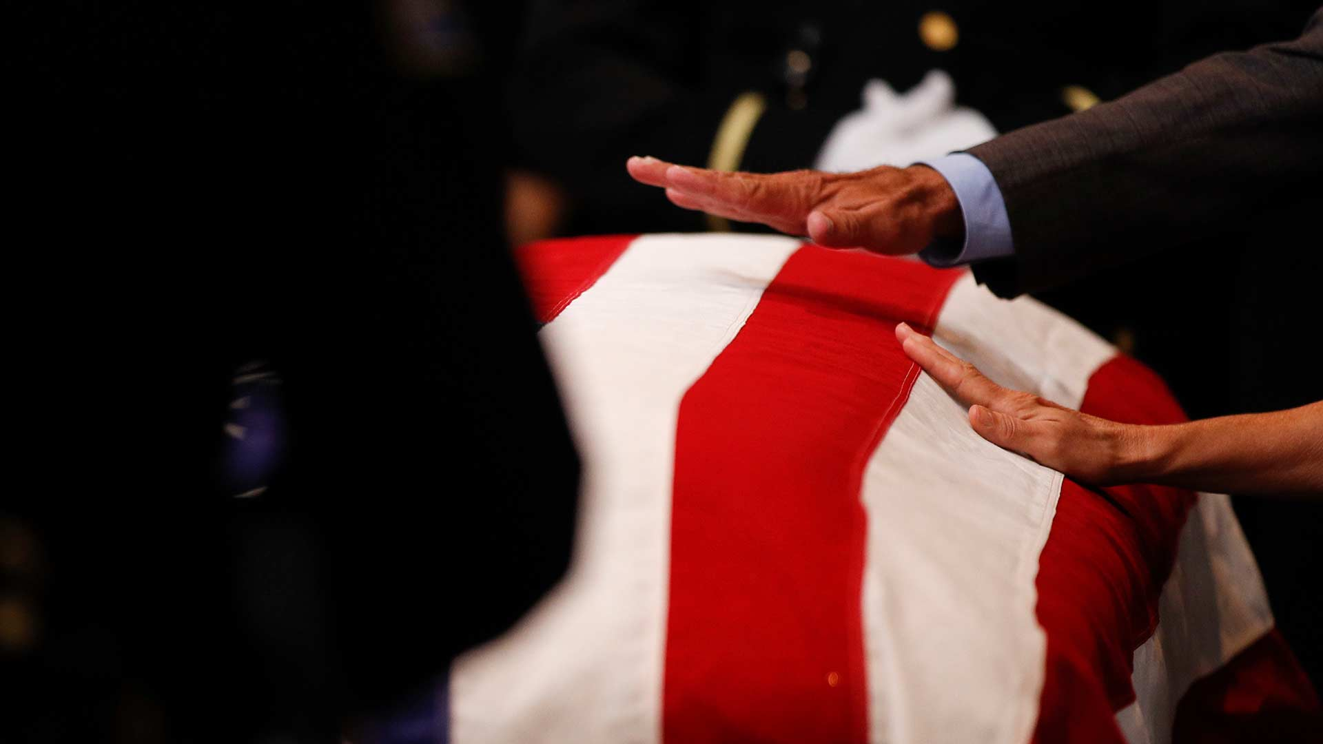 Mourners touch the casket during a memorial service for Sen. John McCain, R-Ariz. at the Arizona Capitol on Wednesday, Aug. 29, 2018, in Phoenix.
