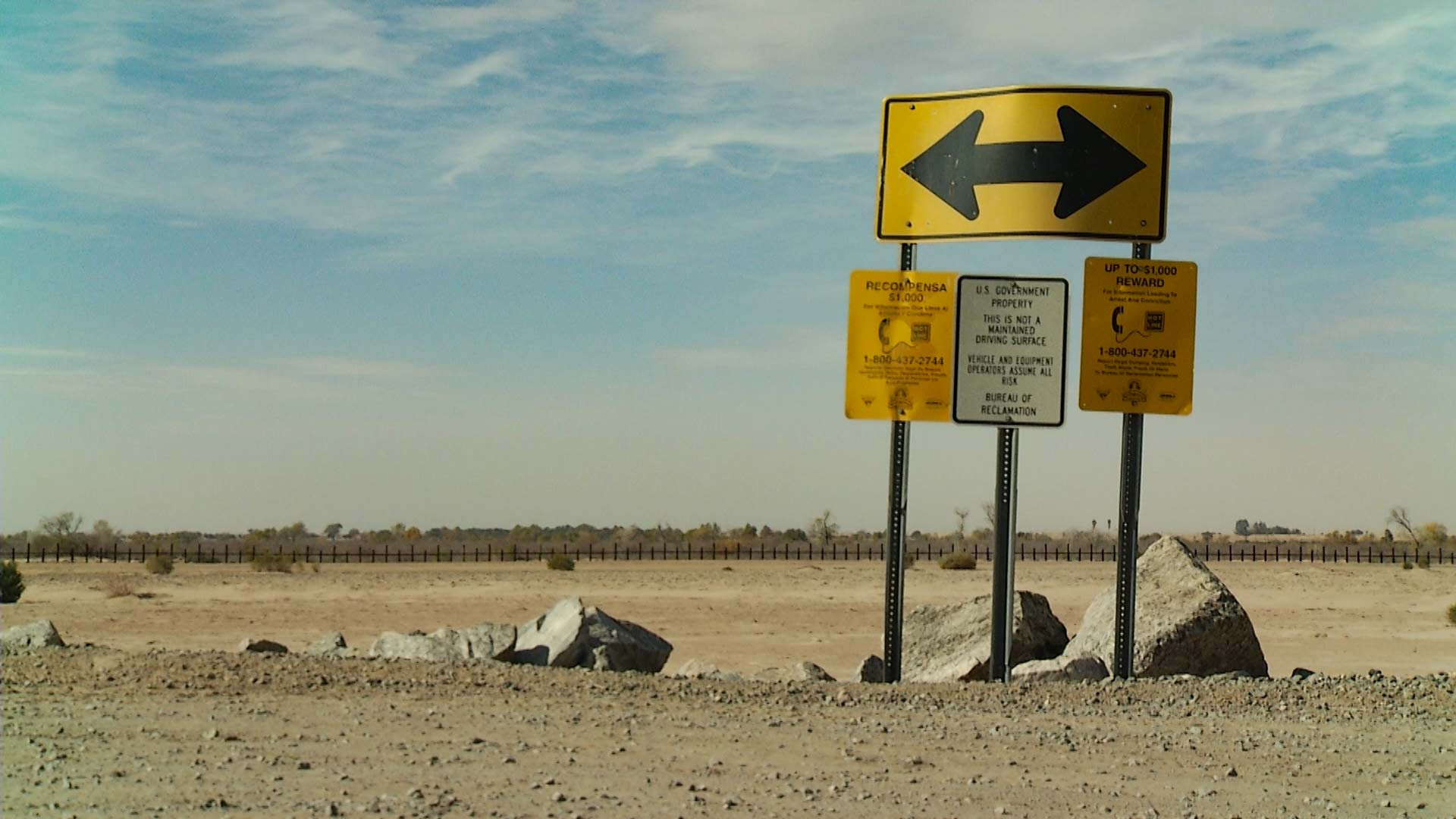Signs posted in the Yuma Sector. In the background, a border vehicle barrier can be seen.
