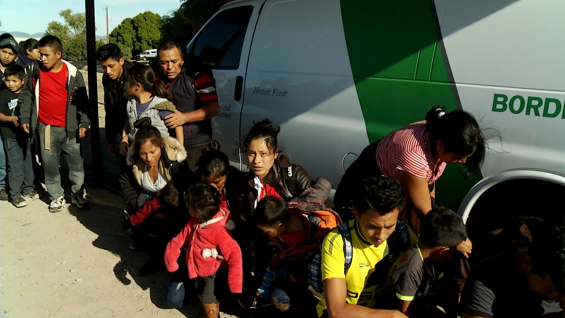 Immigrants from Central America begin to sit in front of a Border Patrol vehicle after surrendering to agents outside of San Luis, Arizona on December 20, 2018.
