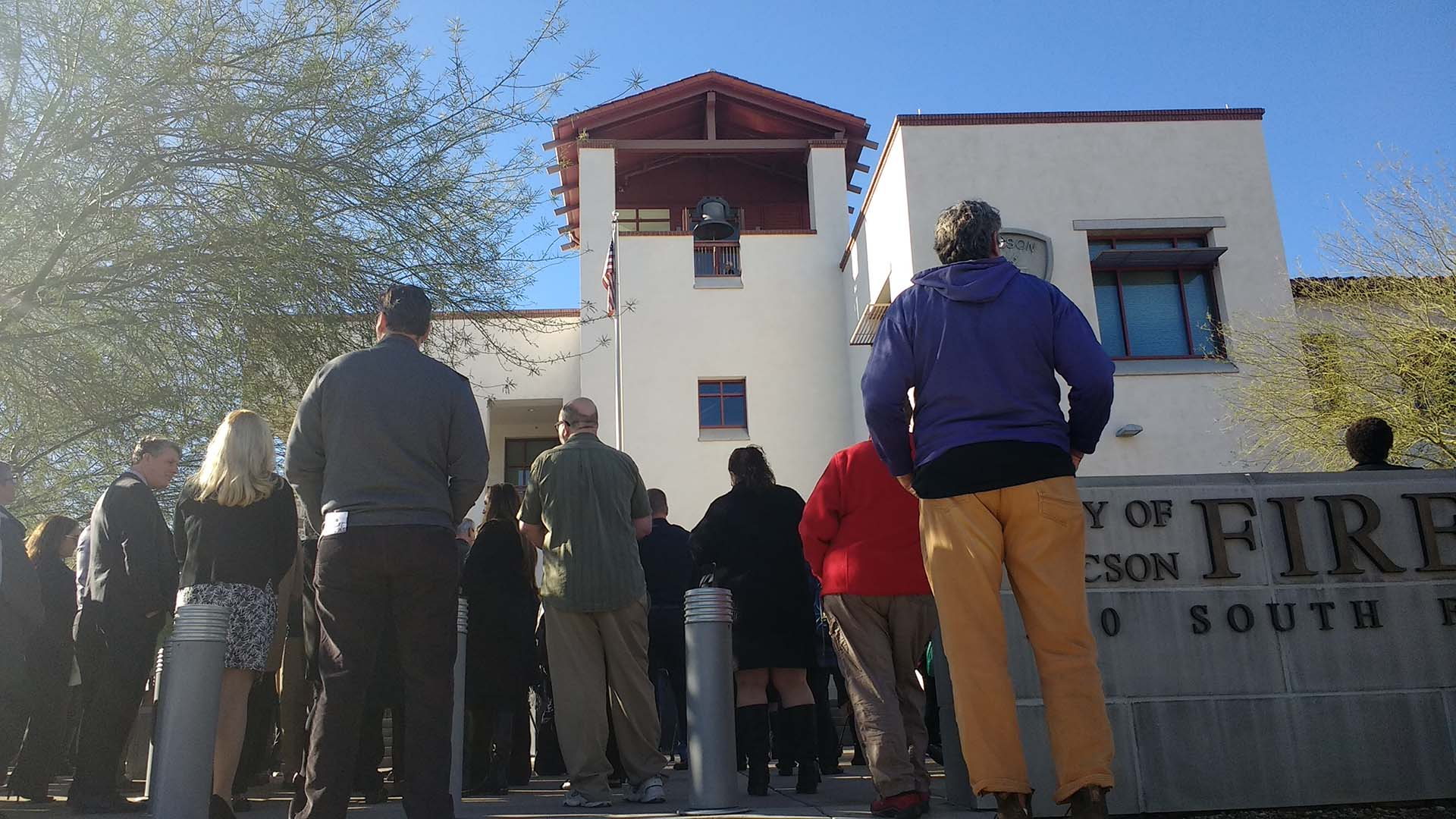 People gather outside Tucson Fire Central under the tower holding the historic fire department bell on January 8, 2019.   The city commemorated the eighth anniversary of the 2011 mass shooting that claimed six lives and left 13 people wounded.