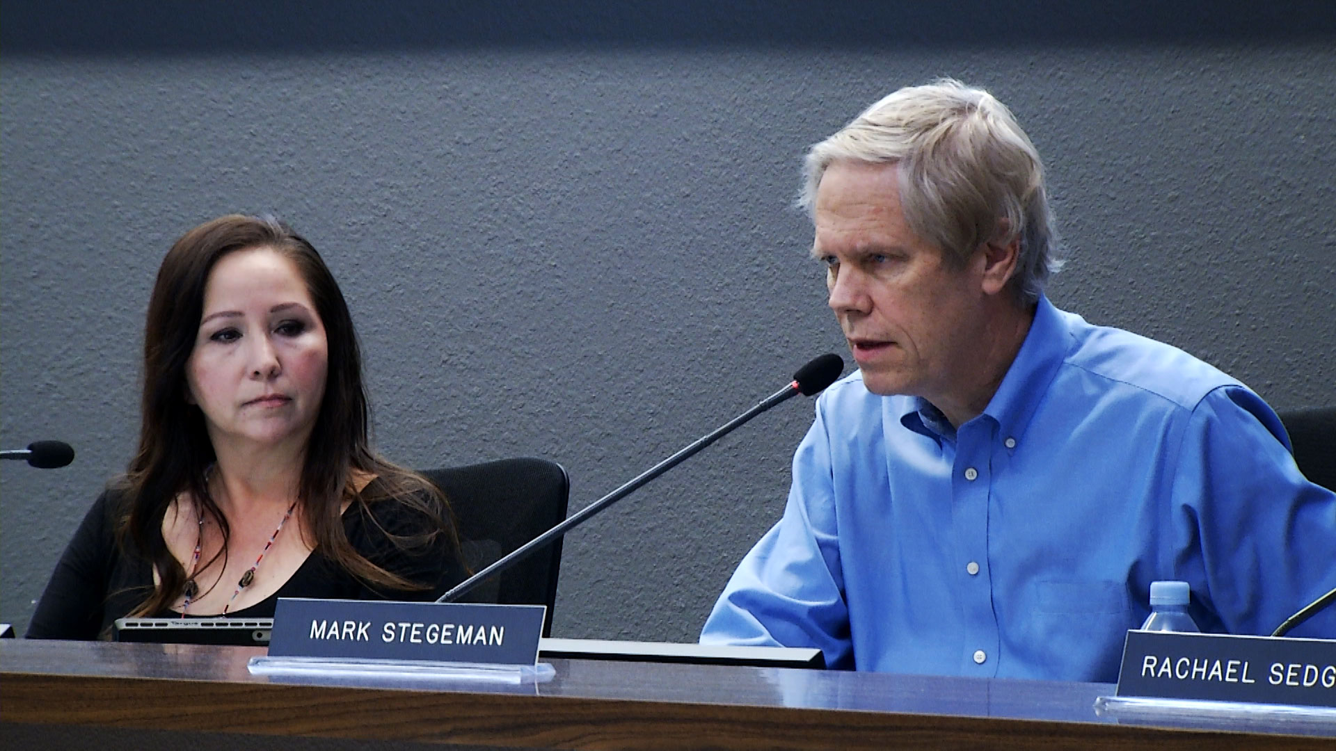 Mark Stegeman speaks into the mic while Adelita Grijalva looks on during a Tucson Unified School District board meeting in January 2019.