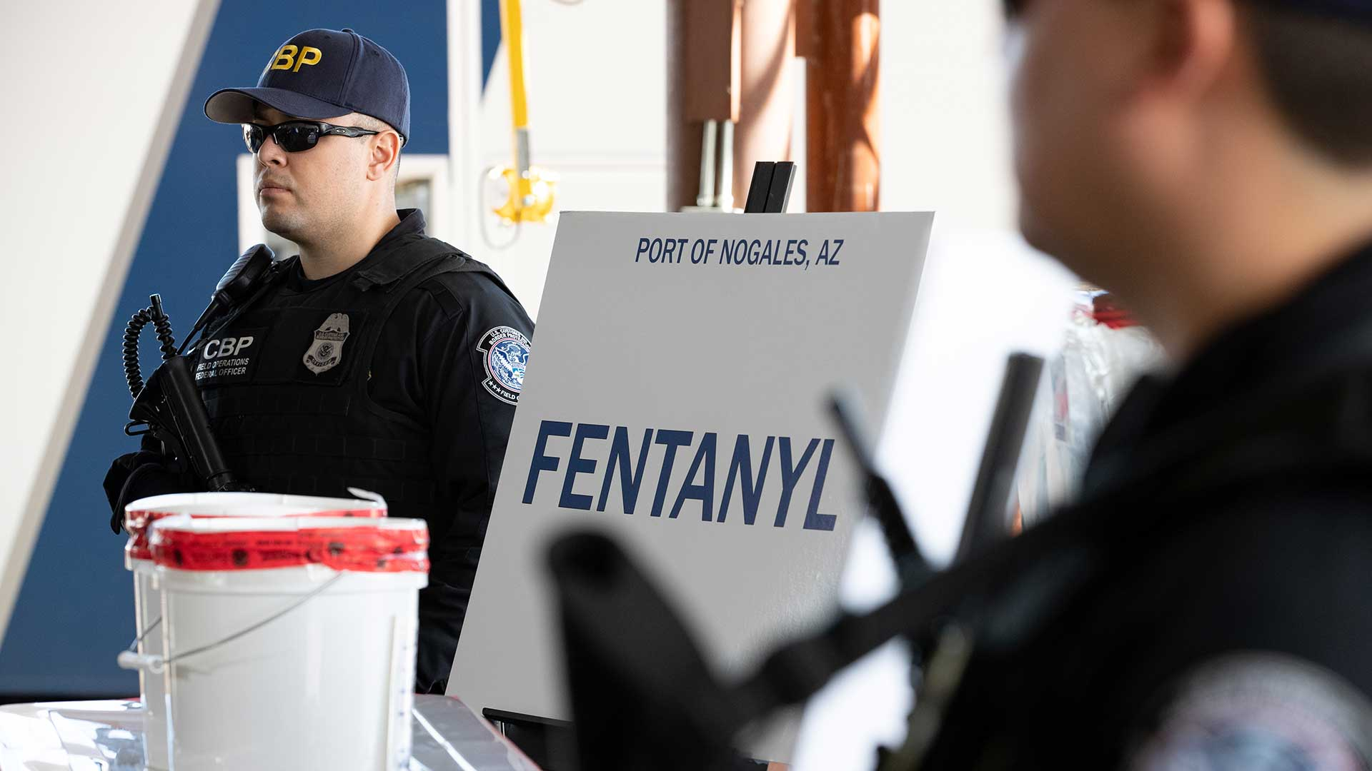 CBP officers stand guard next to fentanyl seized by the agency at the Port of Nogales Jan. 26, 2019.