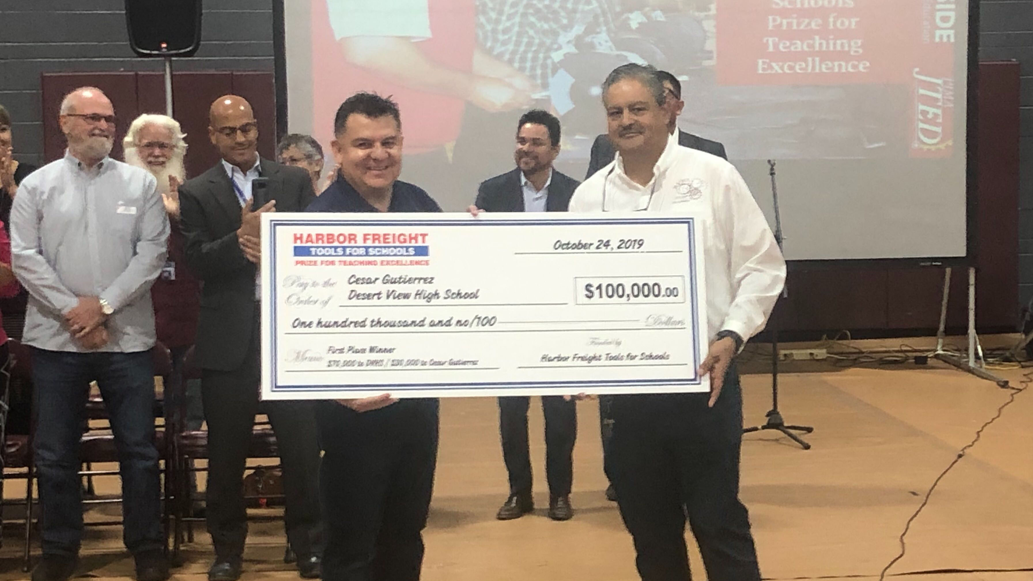 Cesar Gutierrez, right, receives the Harbor Freight Tools For Schools award for teacher excellence.