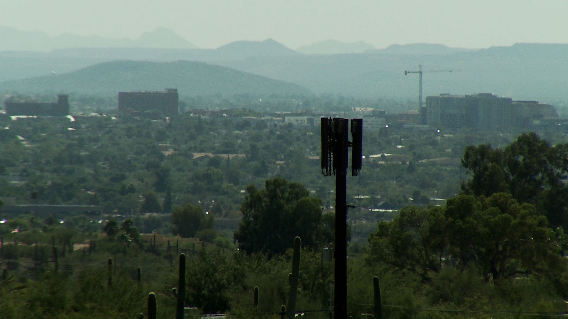 A cell tower is visible in the foreground against the backdrop of the city of Tucson.