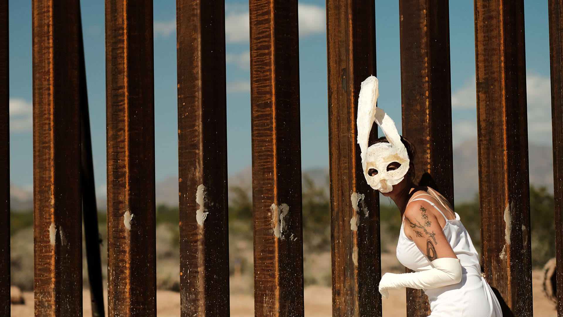 Artist wears a mask representing the jackrabbit at a protest against more border wall construction.