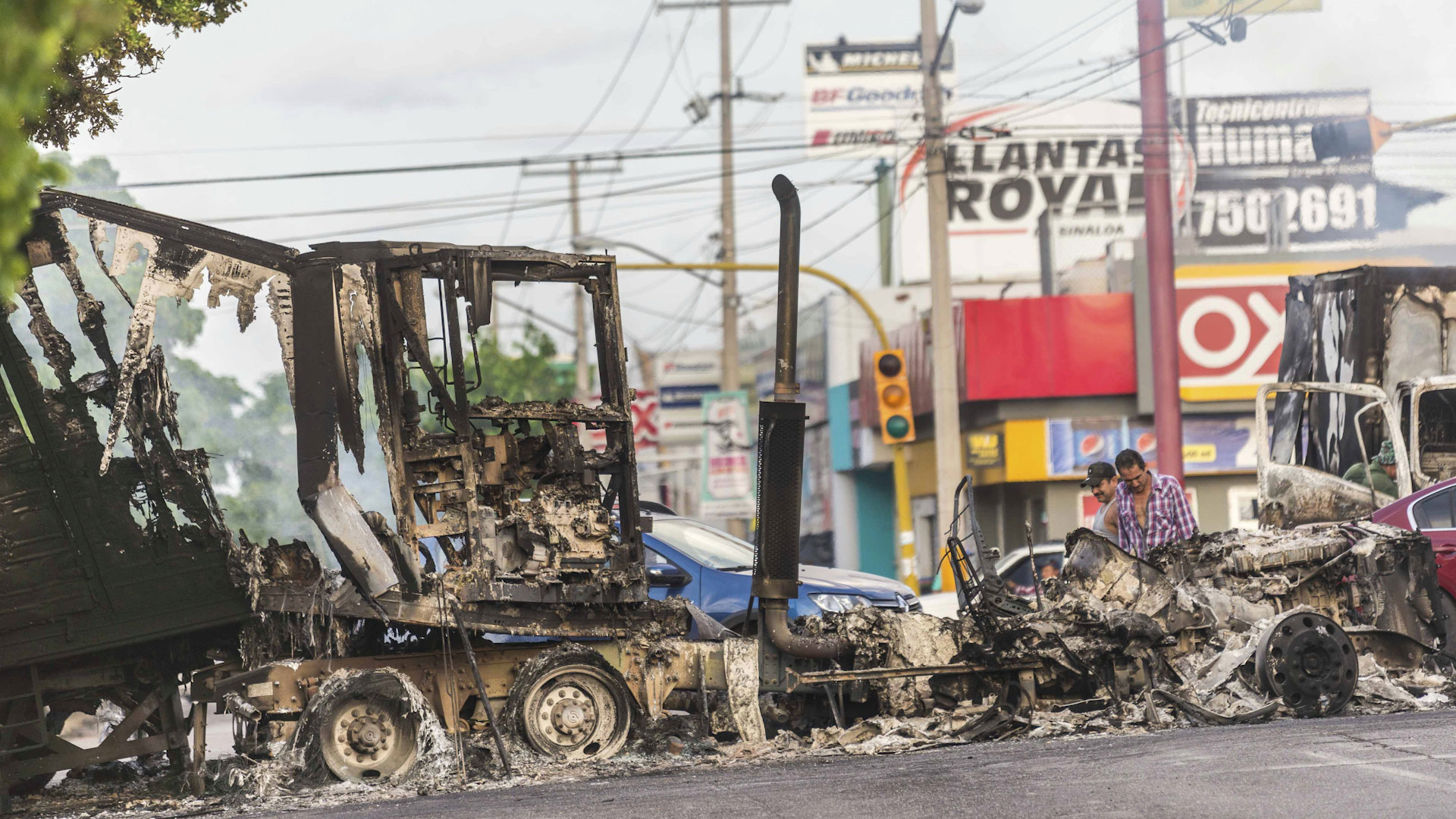 "A burnt out semi truck used by gunmen smolders on an intersection, a day after street battles between gunmen and security forces in Culiacan, Mexico, Friday Oct. 18, 2019. Mexican security forces backed off an attempt to capture a son of imprisoned drug lord Joaquin ""El Chapo"" Guzman after finding themselves outgunned in a ferocious shootout with cartel enforcers that left at least eight people dead and more than 20 wounded, authorities said."