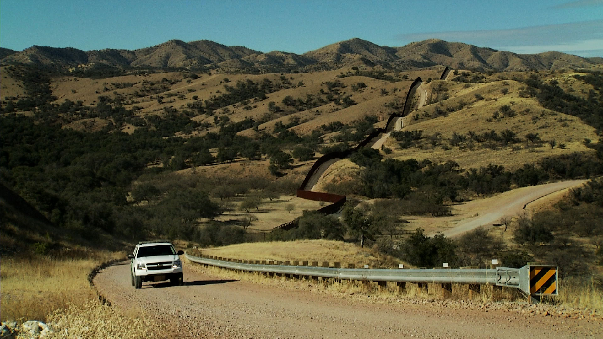 A Border Patrol vehicle drives along a dirt road parallel to the Arizona/Mexico border.