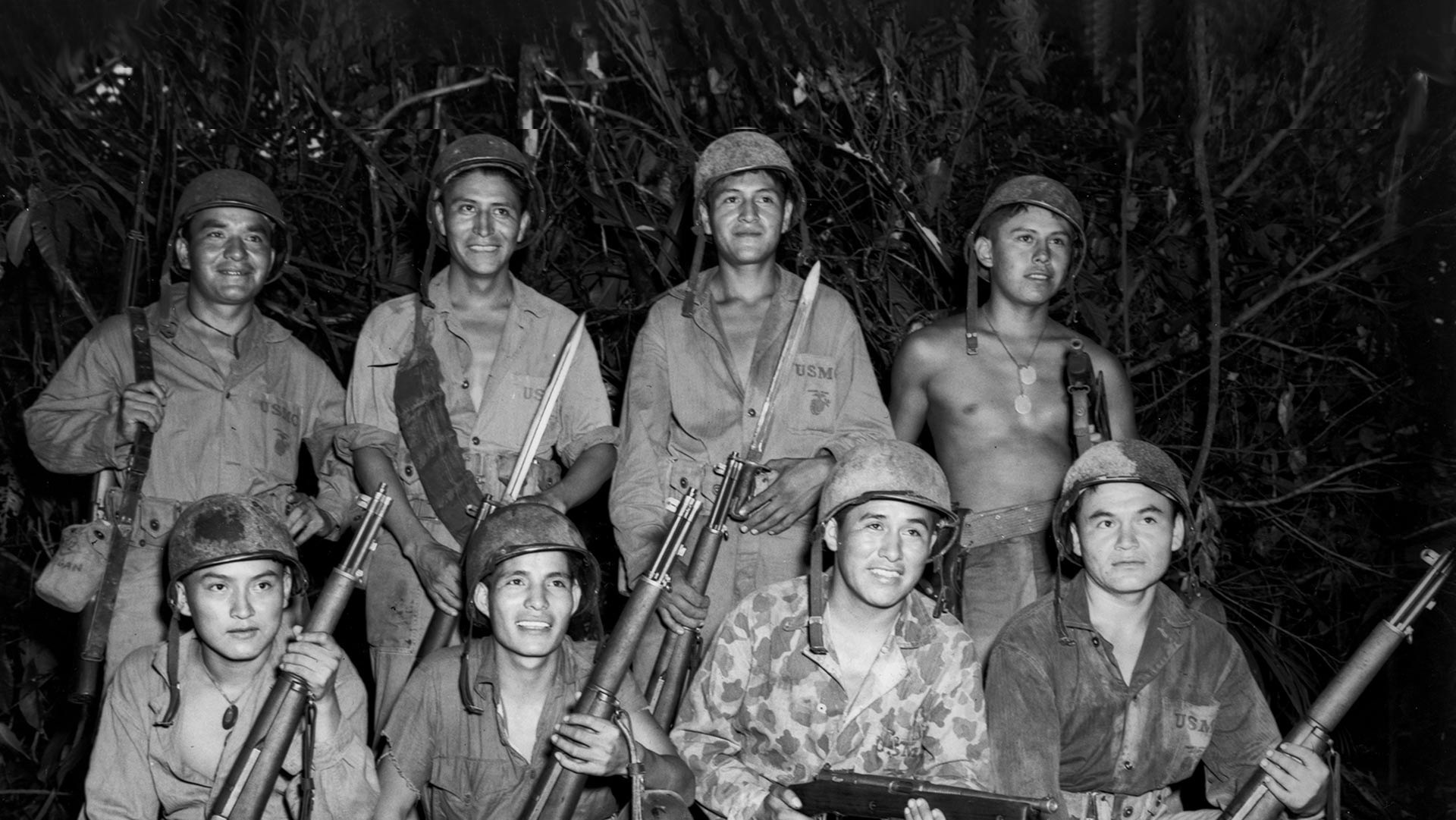 Navajo Marine code talkers on duty at Bougainville, Solomon Islands, c. December 1943. Front row, left to right: Privates Earl Johnny, Kee Etsicitty, John V. Goodluck, and Private First Class David Jordan. Back row: Privates Jack C. Morgan, George H. Kirk, Tom H. Jones, and Corporal Henry Bake, Jr.