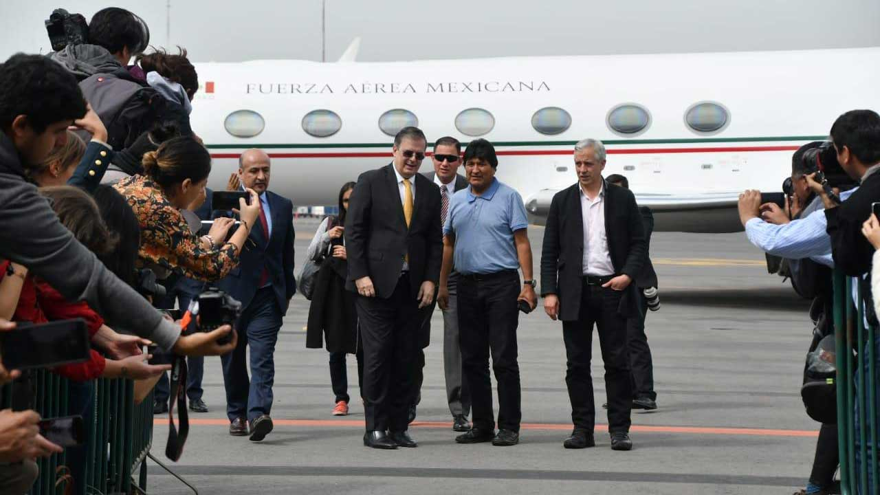 Mexican Foreign Relations Secretary Marcelo Ebrard, center left, welcomes former Bolivian President Evo Morales, center right, at the Mexico City airport on Tuesday.