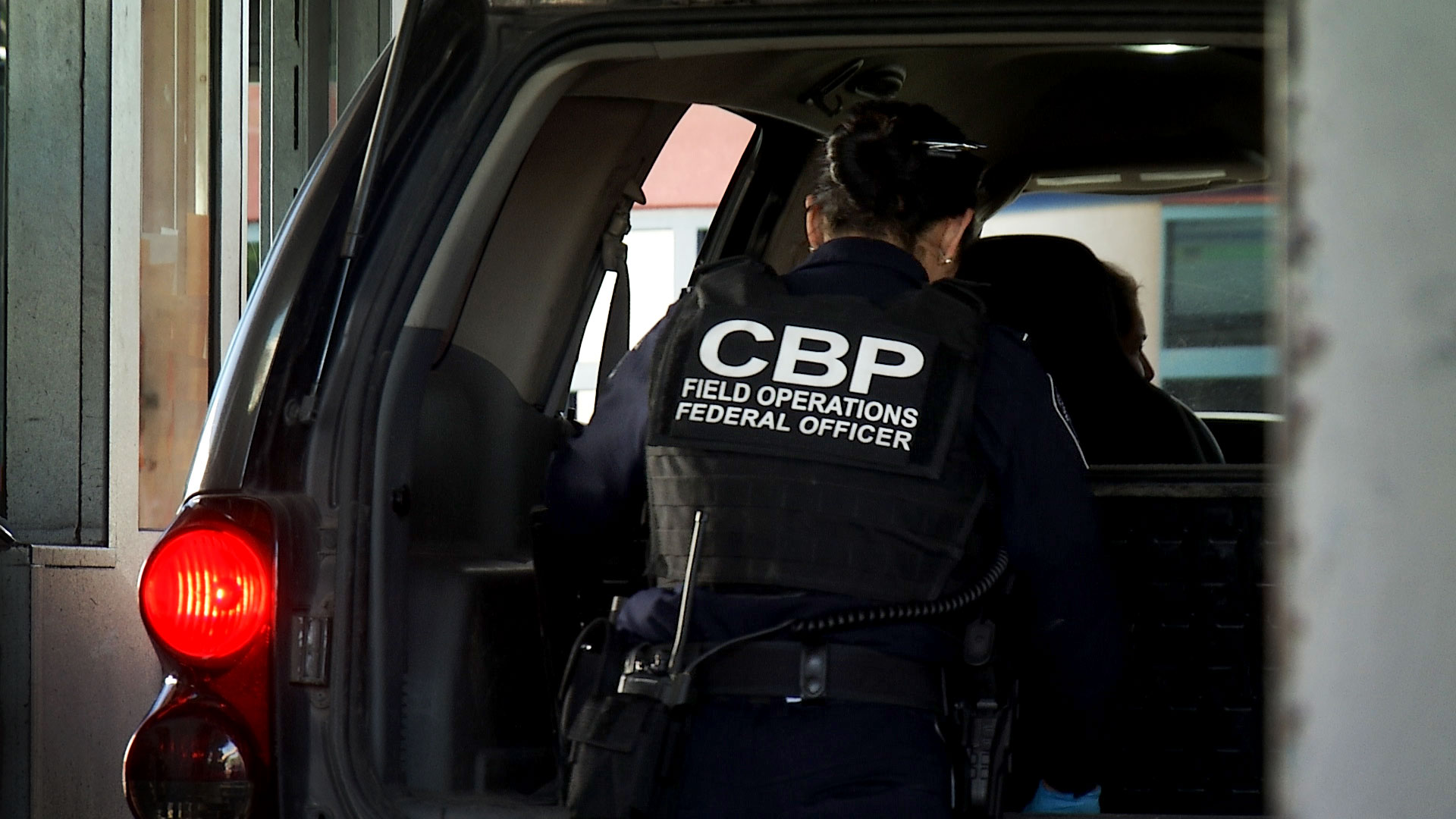 A Customs and Border Protection officer inspects a vehicle at the Dennis DeConcini Port of Entry in May 2019.