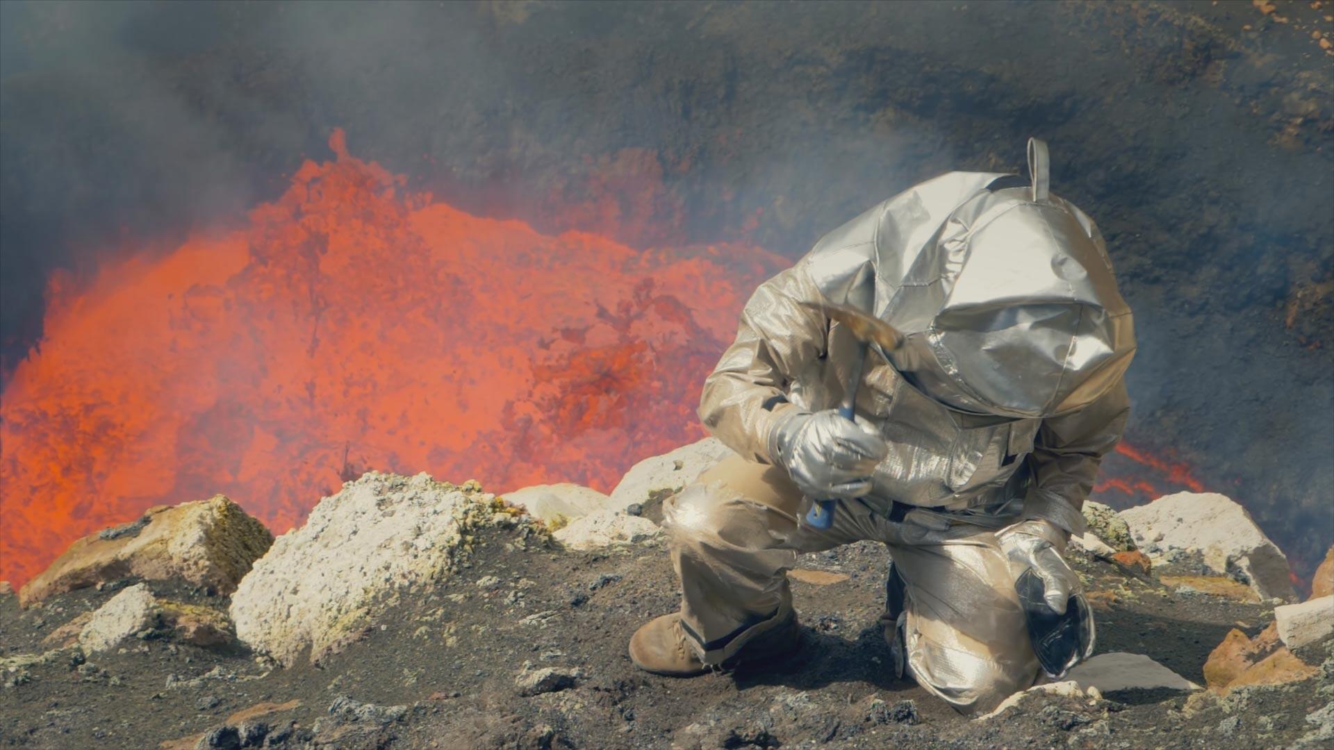 Scientist Dr. Jeffrey Marlow takes samples with the bubbling lava lake of Marum, Vanuatu behind him.
