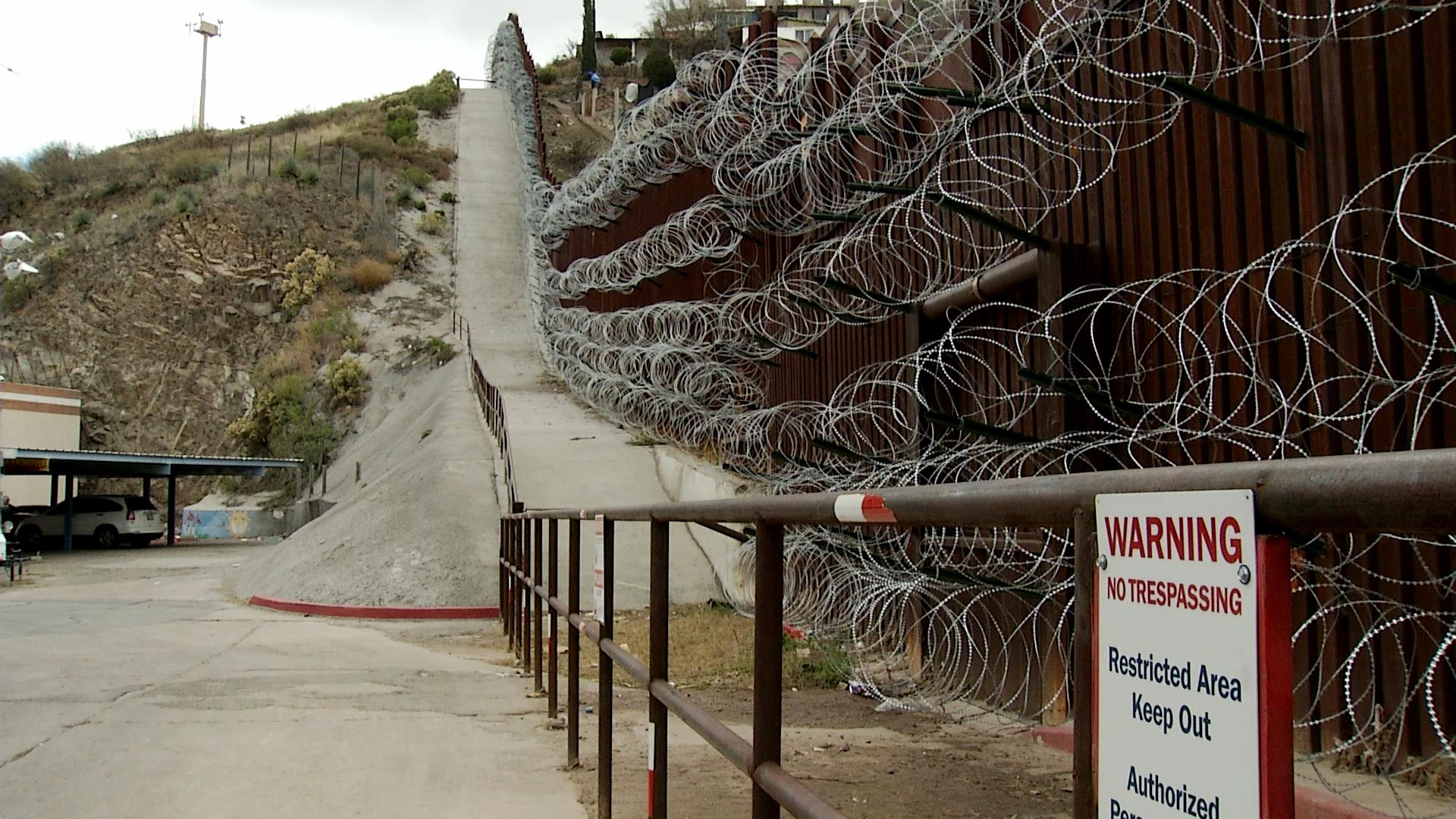 A sign warns against trespassing on federal property in front of bollard fencing covered in concertina wire at the international border in Nogales, Arizona.
