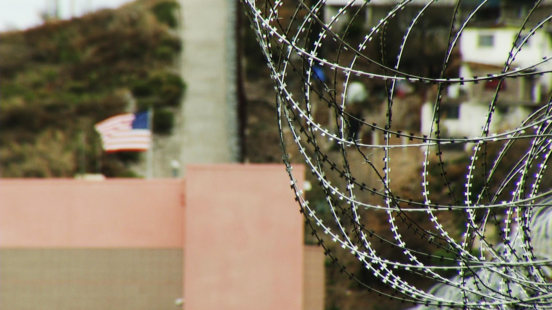 Concertina wire lines bollard fencing at the international border in Nogales, Arizona.
