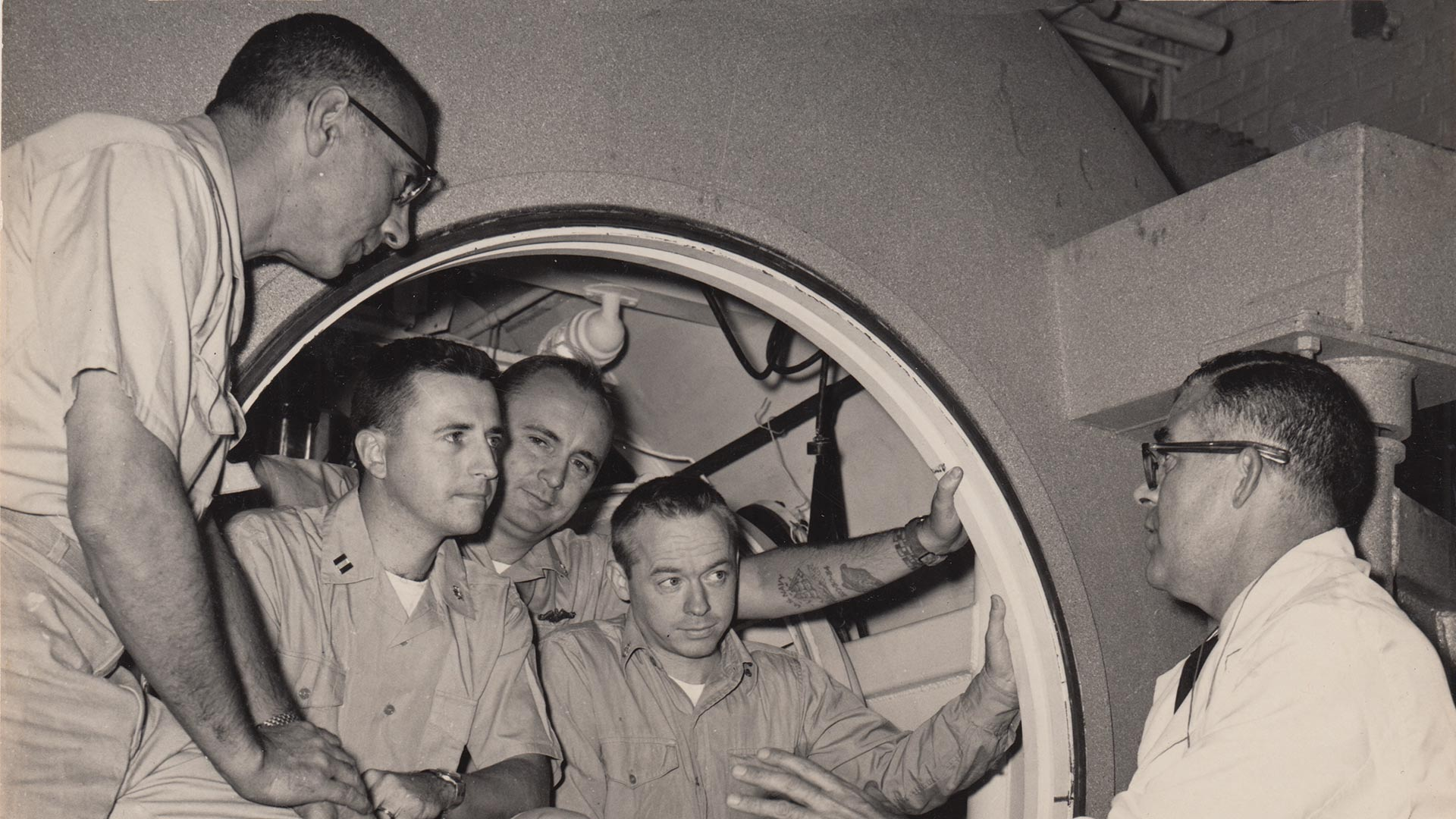 Walter Mazzone, Raymond Lavoi, Bob Barth, Sanders Manning, and George Bond, at the entrance of the Genesis E chamber, 1961.