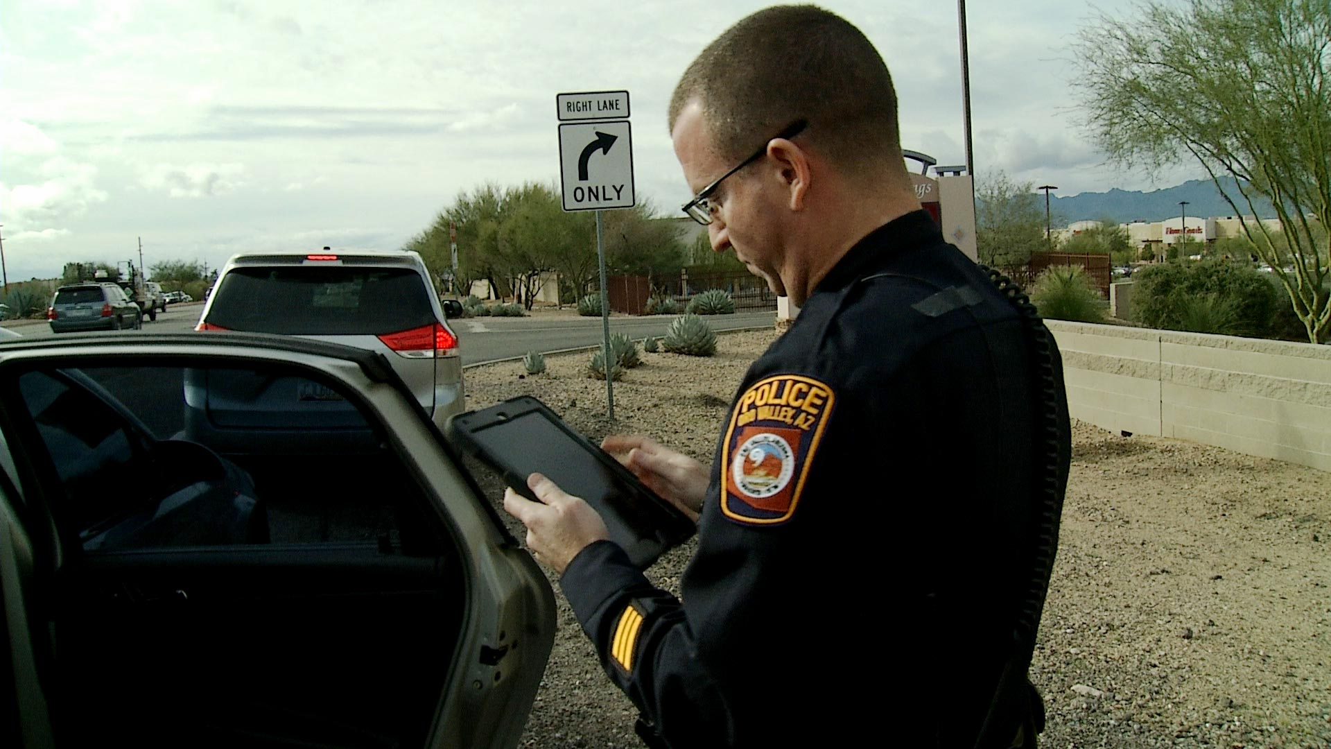 Officer Brian Kleinberg, with the Oro Valley Police Dept. Traffic Unit, looks up information on a tablet shortly after pulling over a driver suspected of violating the town's ban on using a mobile device while driving on February 5, 2019.
