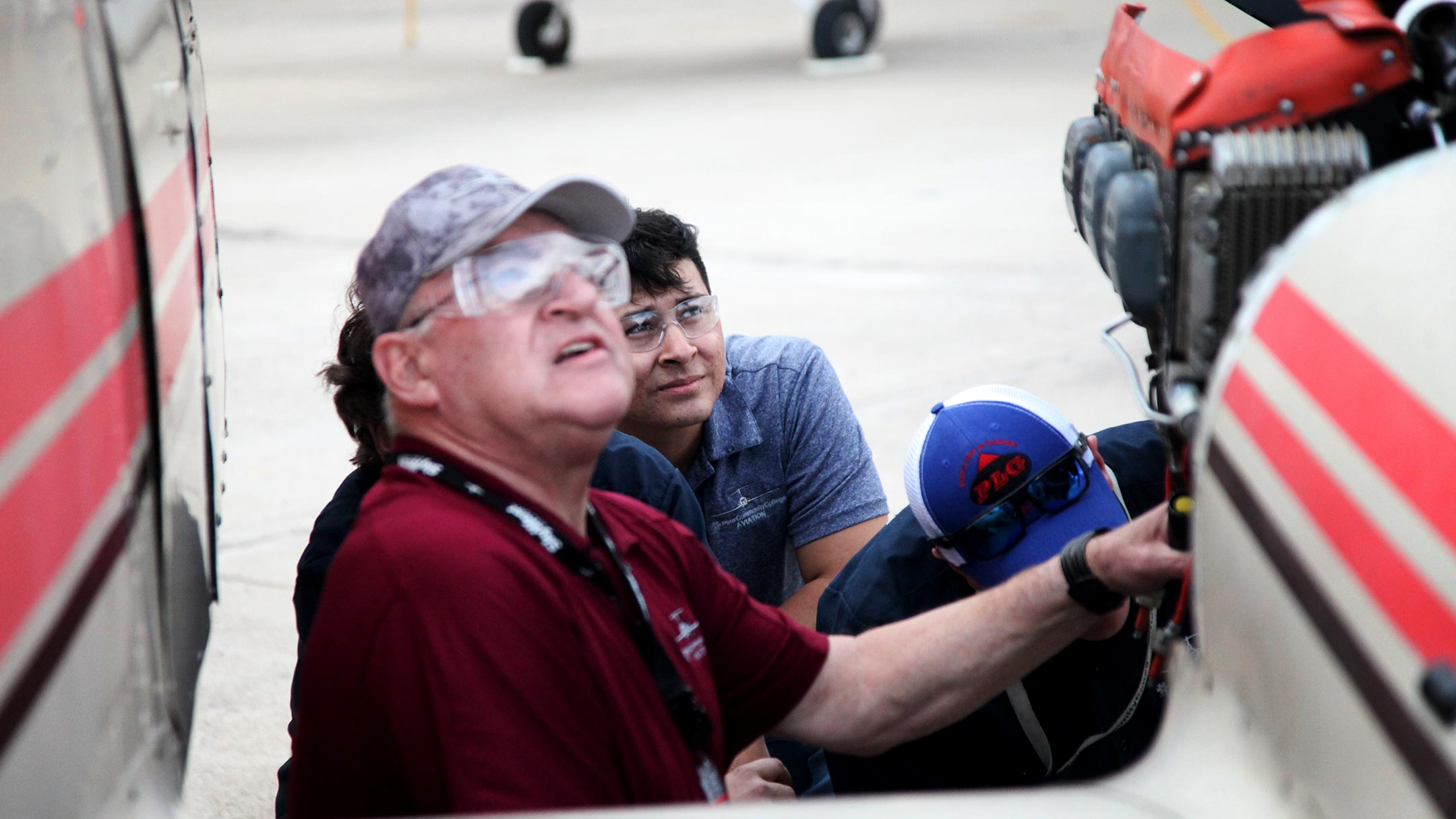 Students and an instructor at Pima Community College's aviation technology program watch a plane pass above as they perform maintenance on a small aircraft at the college's facility near Tucson International Airport on Feb. 4, 2019.