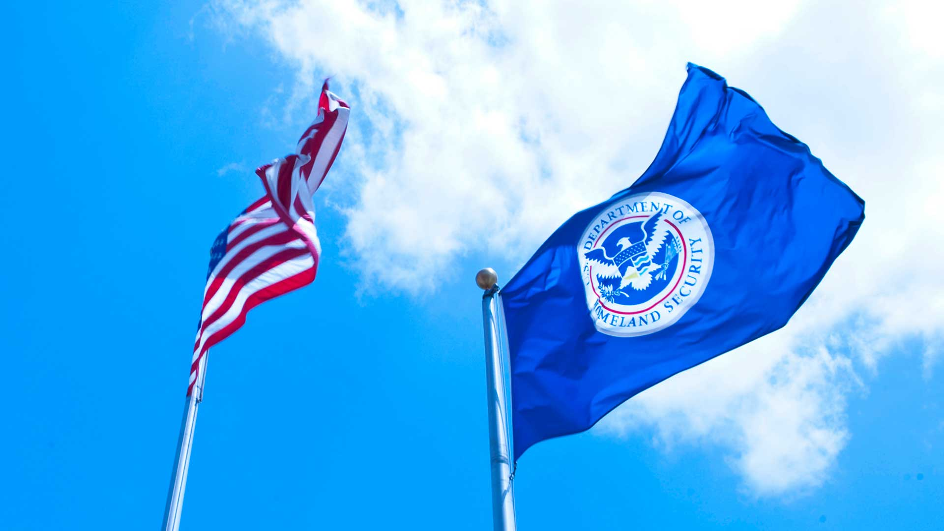 The American flag and a flag bearing the seal of the Department of Homeland Security.