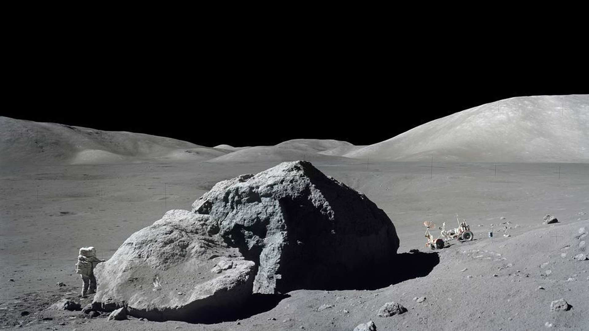 Harrison H. Schmitt stands next to a split lunar boulder on the Apollo 17 mission in this photo from Dec. 13, 1972.