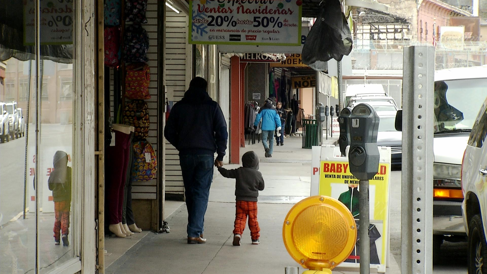 A man and child walk along storefronts in Nogales, Arizona on February 18, 2019.