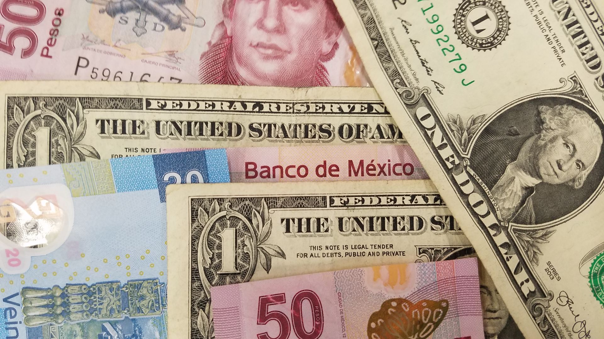 File image of Mexican pesos and American dollars.