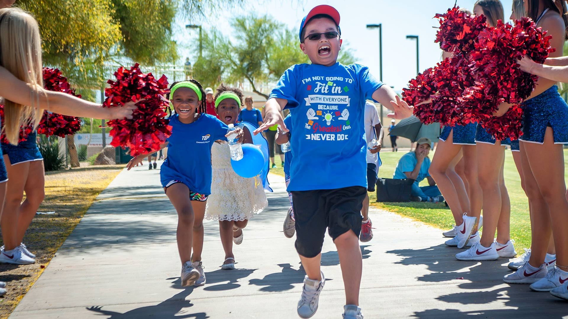 Happy kids receive cheers at the finish line of the annual autism walk, hosted by The Autism Society of Southern Arizona.