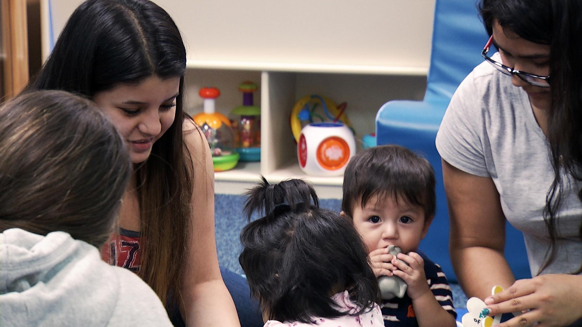 Yosmara Reyes (left), 17, and Corina Perez, 18, interact with their children in the Infant Center operated by Sunnyside High School's Teenage Parent Program on March 5, 2019.