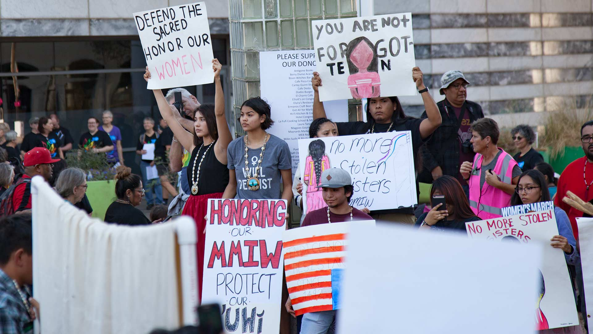 "Demonstrators at the 2019 Tucson Women's March carry signs reading ""MMIW"" (""missing and murdered Indigenous women"") and ""no more stolen sisters."""