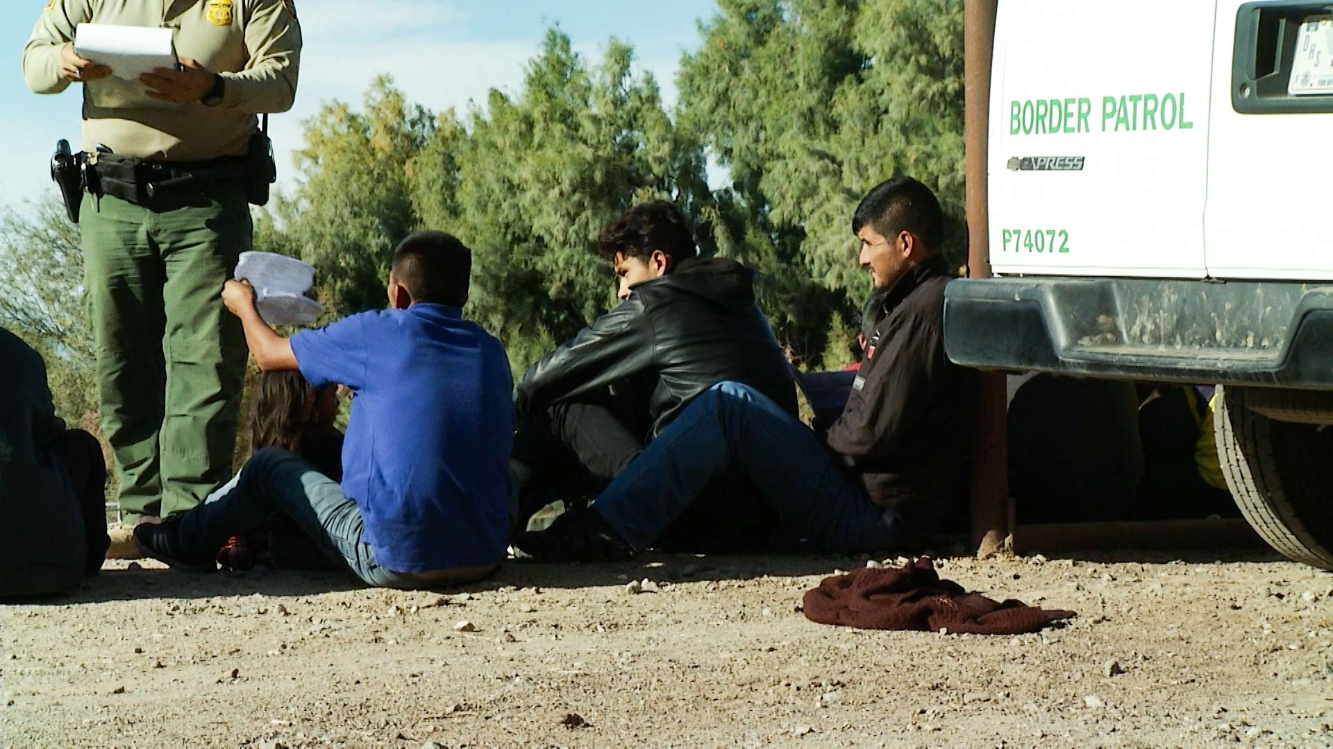 A group of men, women and children prepare their documents after approaching and surrendering to Border Patrol in the Yuma Sector, 2019.