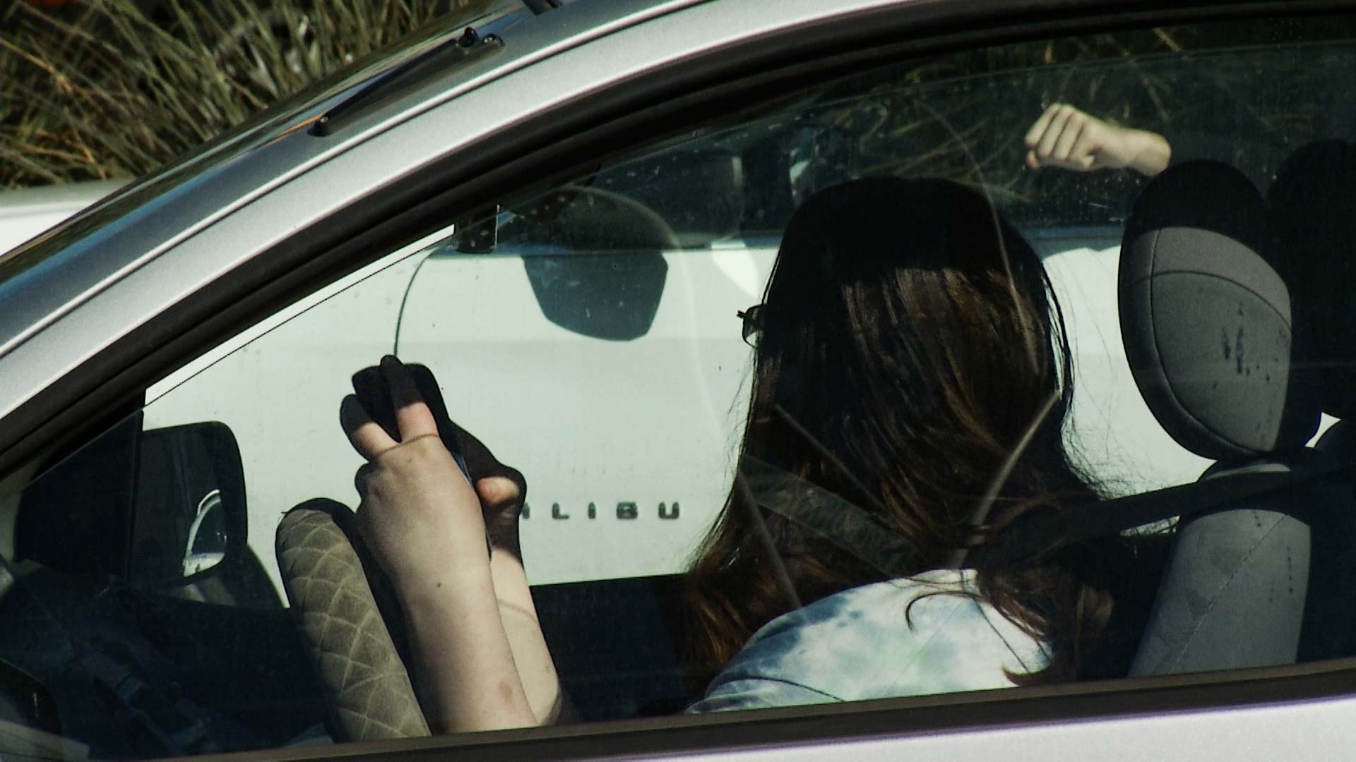 A motorist pulls out a cell phone on a Tucson road.